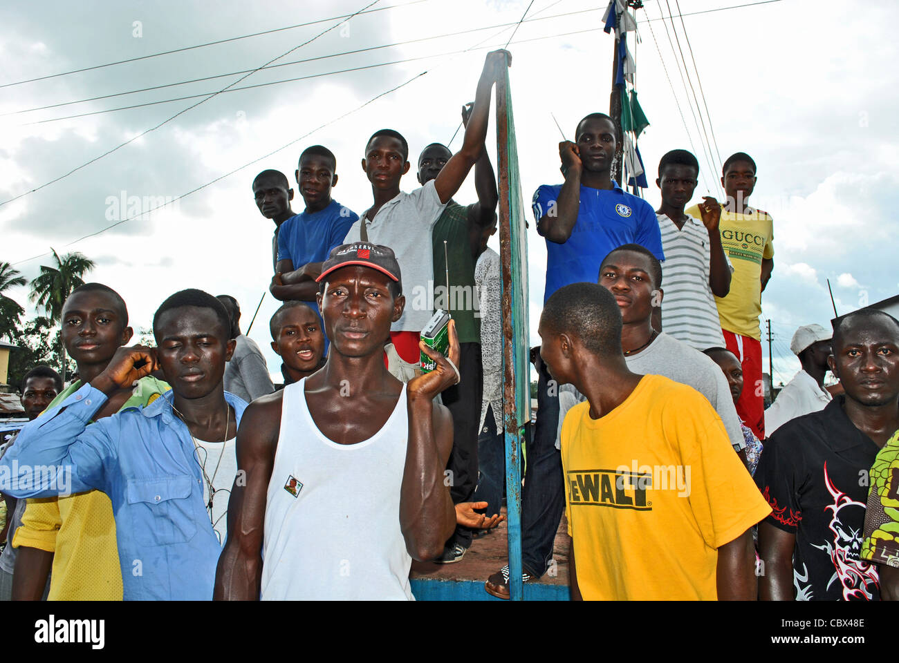 Men listen to breaking news as political violence flares in Bo ahead of elections in 2012, Sierra Leone - Stock Image