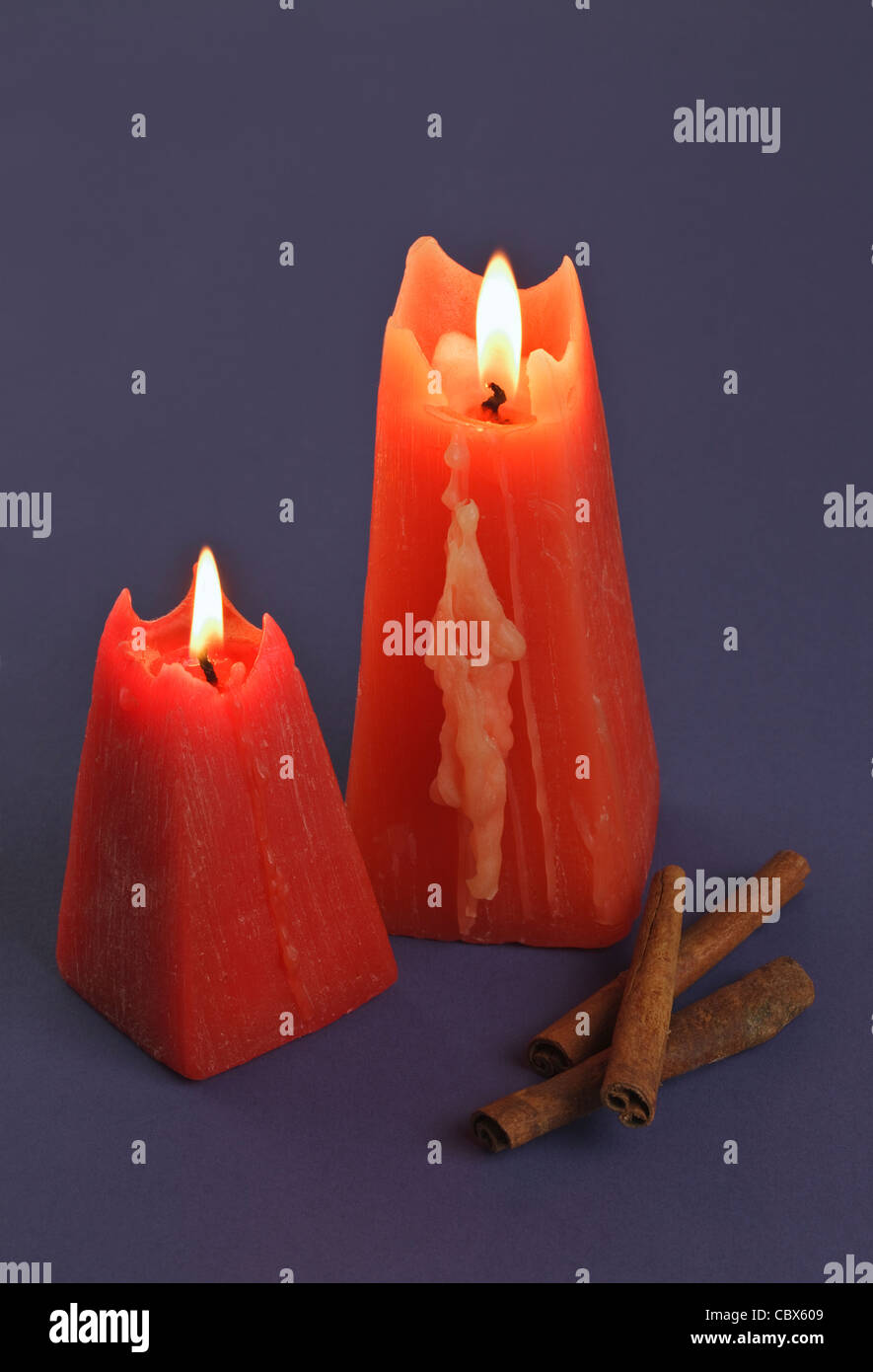Two burning red Candles with Cinnamon sticks - Stock Image