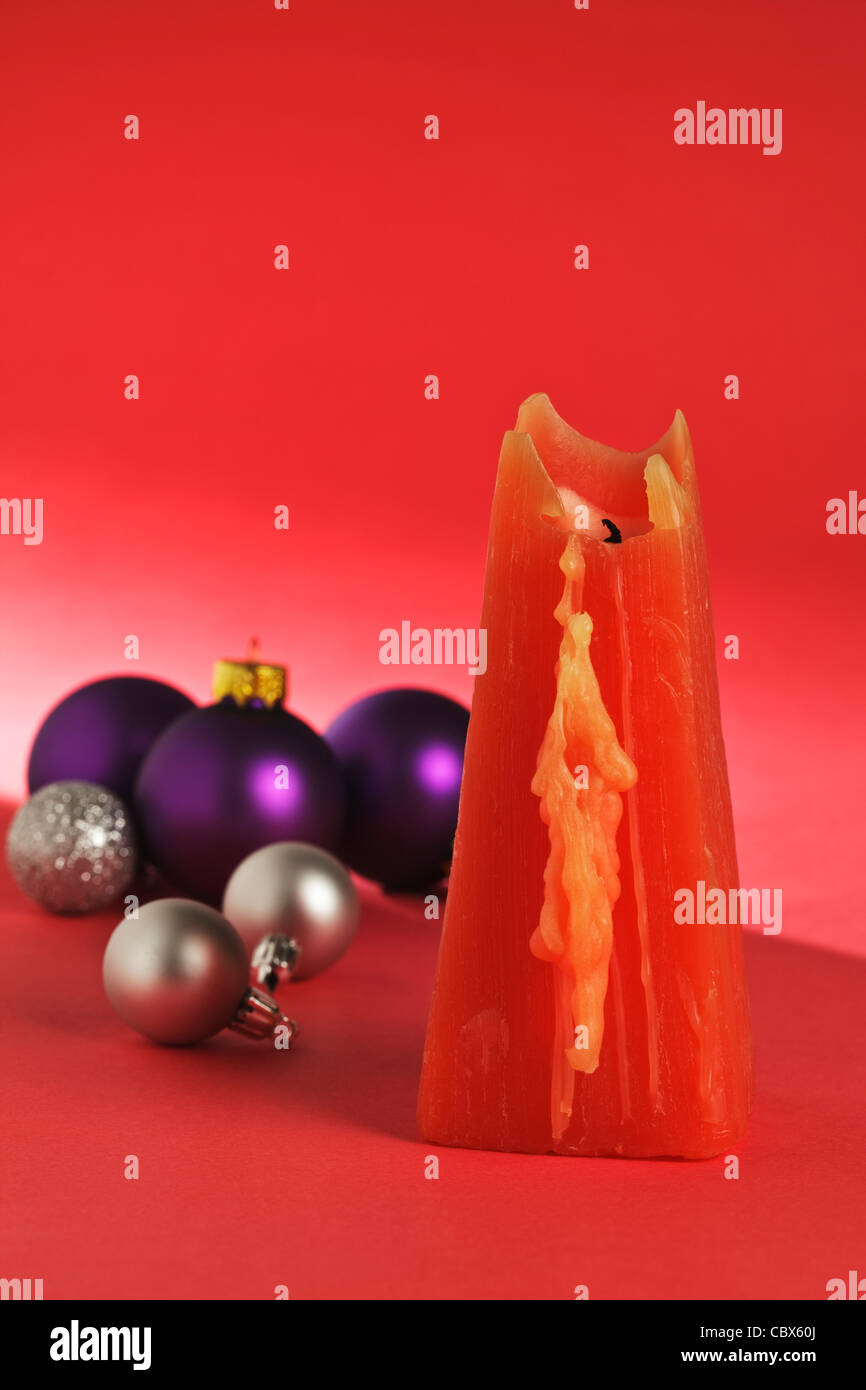 One red Candle with Christmas Baubles - Stock Image