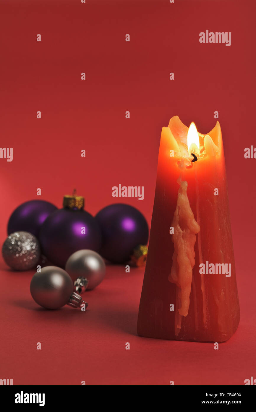 One burning red Candle with Christmas Bubbles - Stock Image