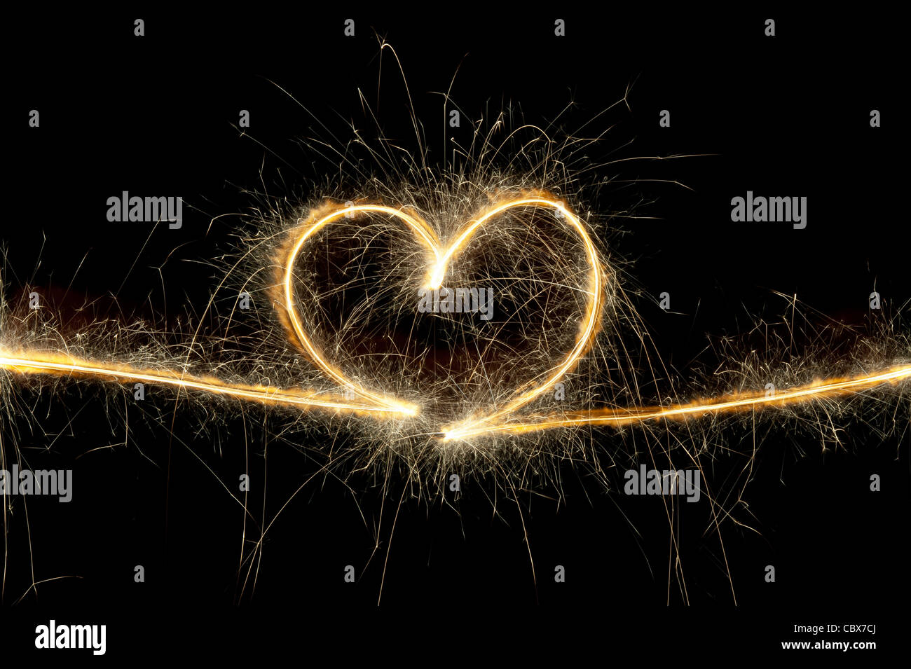 Heart shape made with sparkler at night. Stock Photo