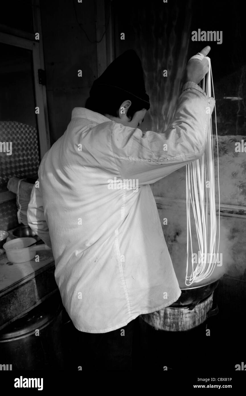 Fatou Qiao, Beijing. Mr. Adili Jiang, an Uyghur cook in a Muslim restaurant, is making noodles. - Stock Image