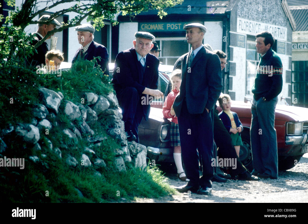 A group of men and boys gather by the post office after Sunday Mass in Cromane Co Kerry Ireland - Stock Image