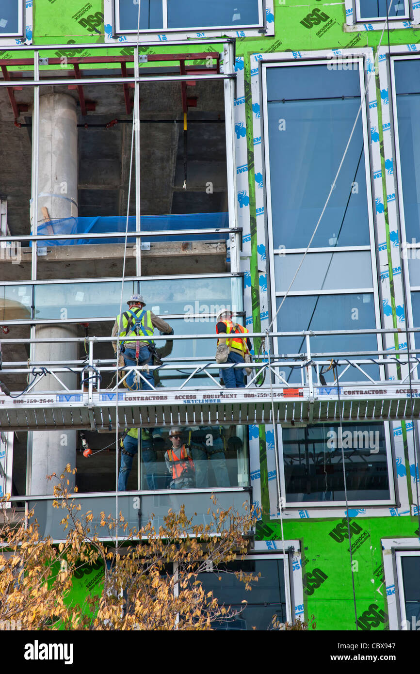 High-rise construction, workers installing ceiling to floor windows. - Stock Image