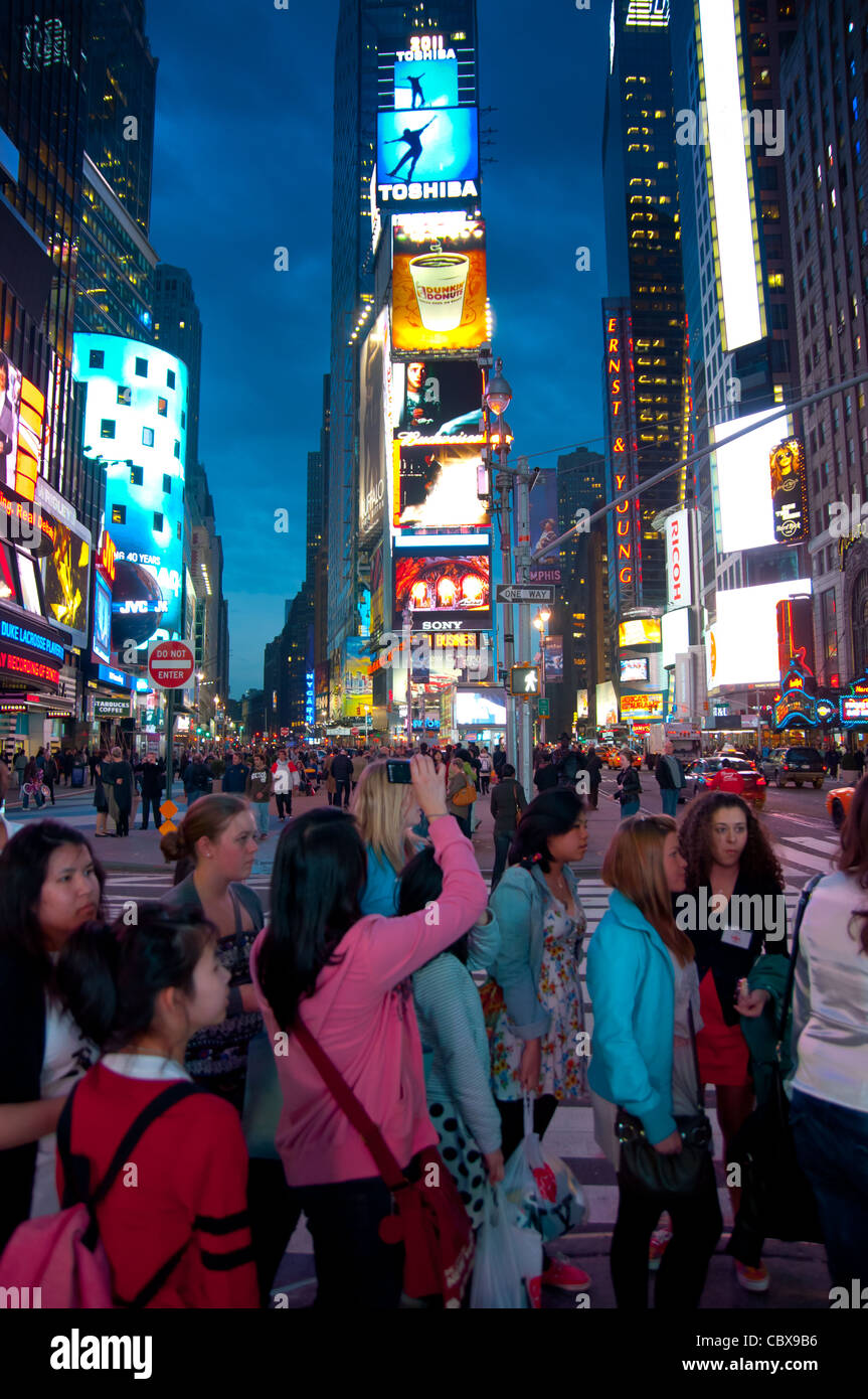 Tourists from Asia taking pictures on Times Square in New York City, USA Stock Photo