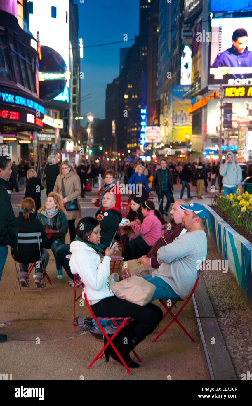 People sitting in chairs in street café on Times Square, New York City, USA Stock Photo