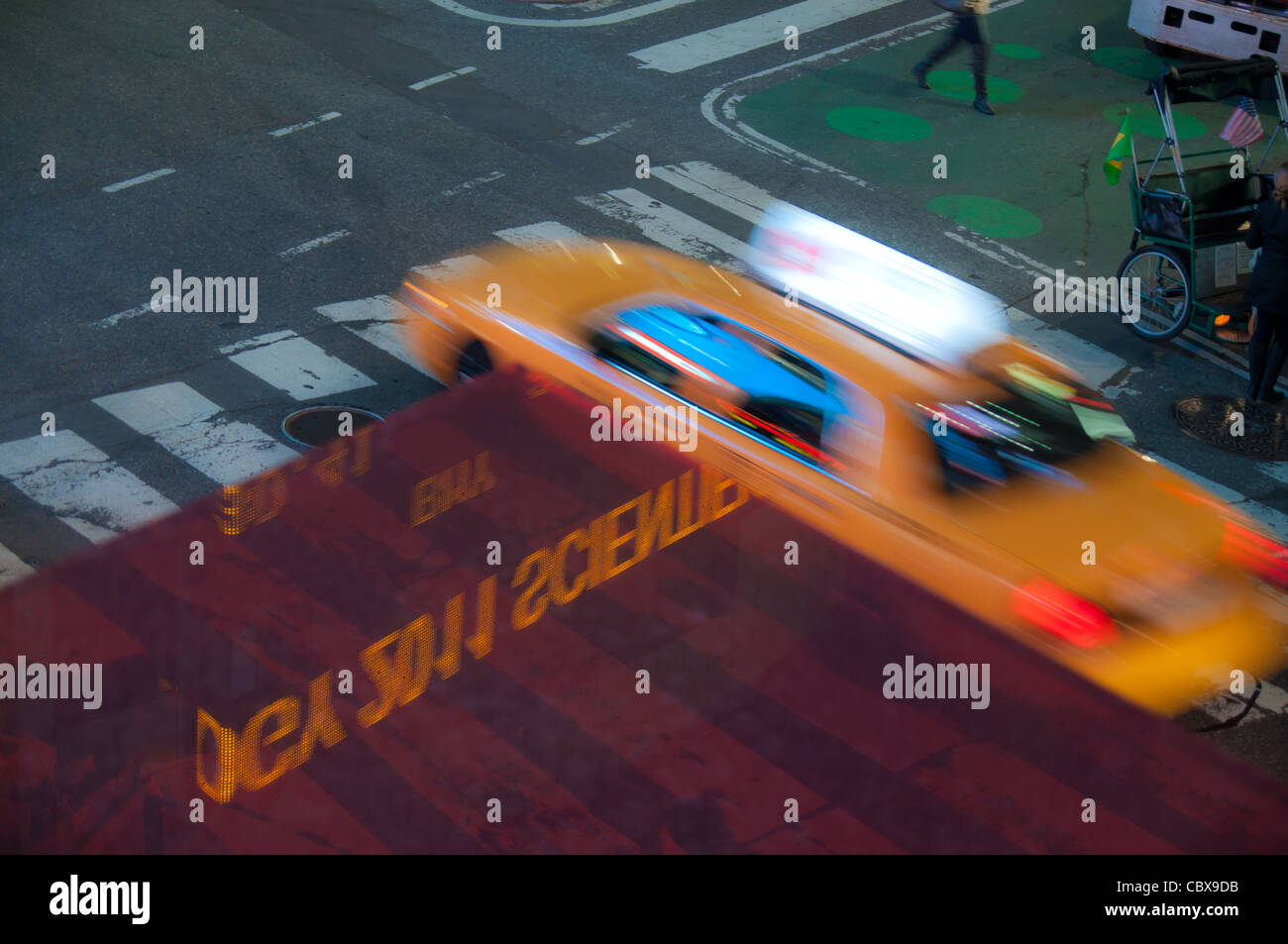 Blurred taxi in motion and stock info reflection on Times Square, New York City Stock Photo
