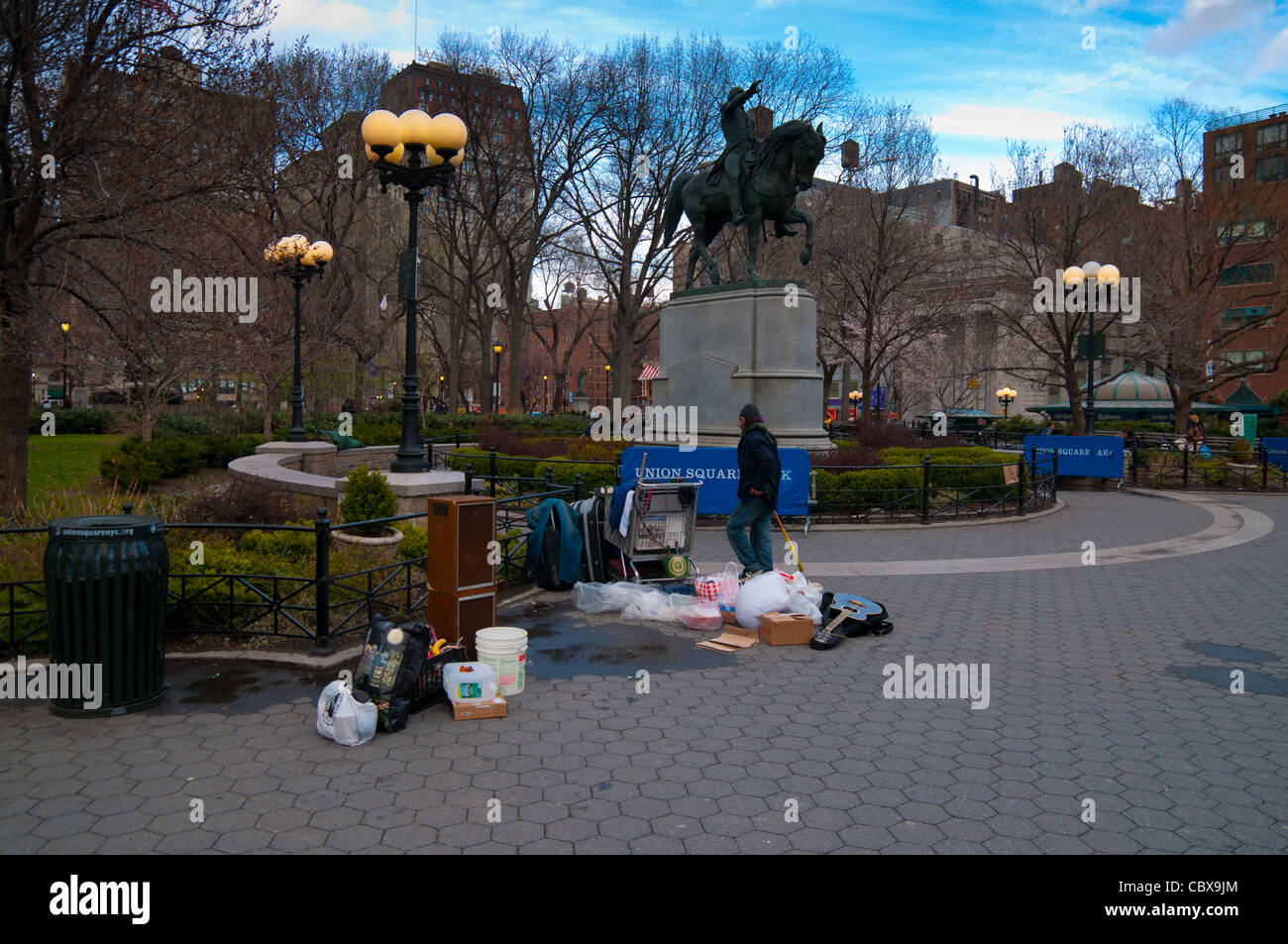 Hobo near the Statue of George Washington in the park of Union Square in Manhattan, New York City - Stock Image