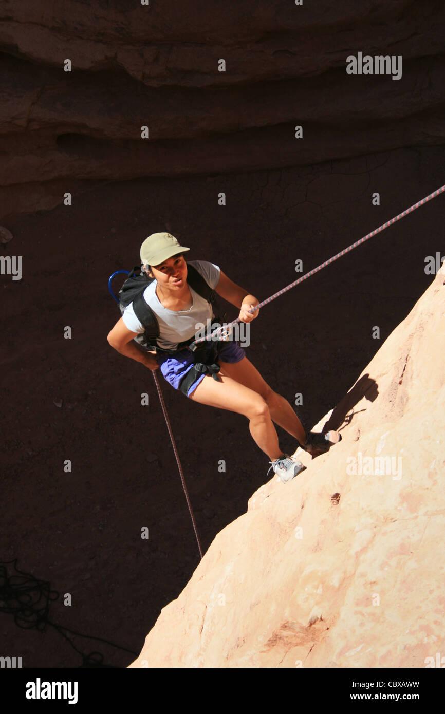 canyoneering asian woman rappels into a shadowed canyon bottom - Stock Image