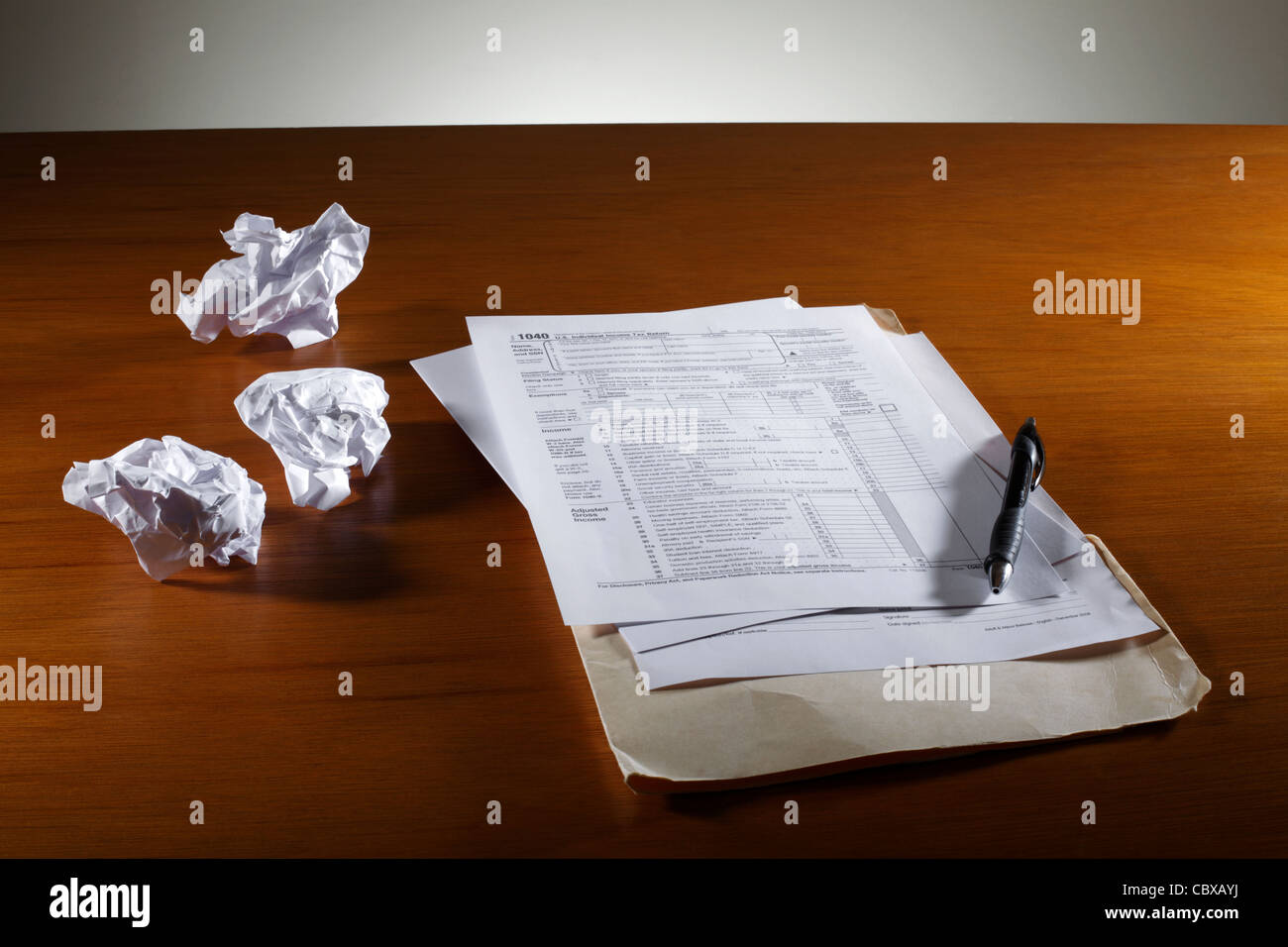 Crumpled paper and tax form on desk - Stock Image