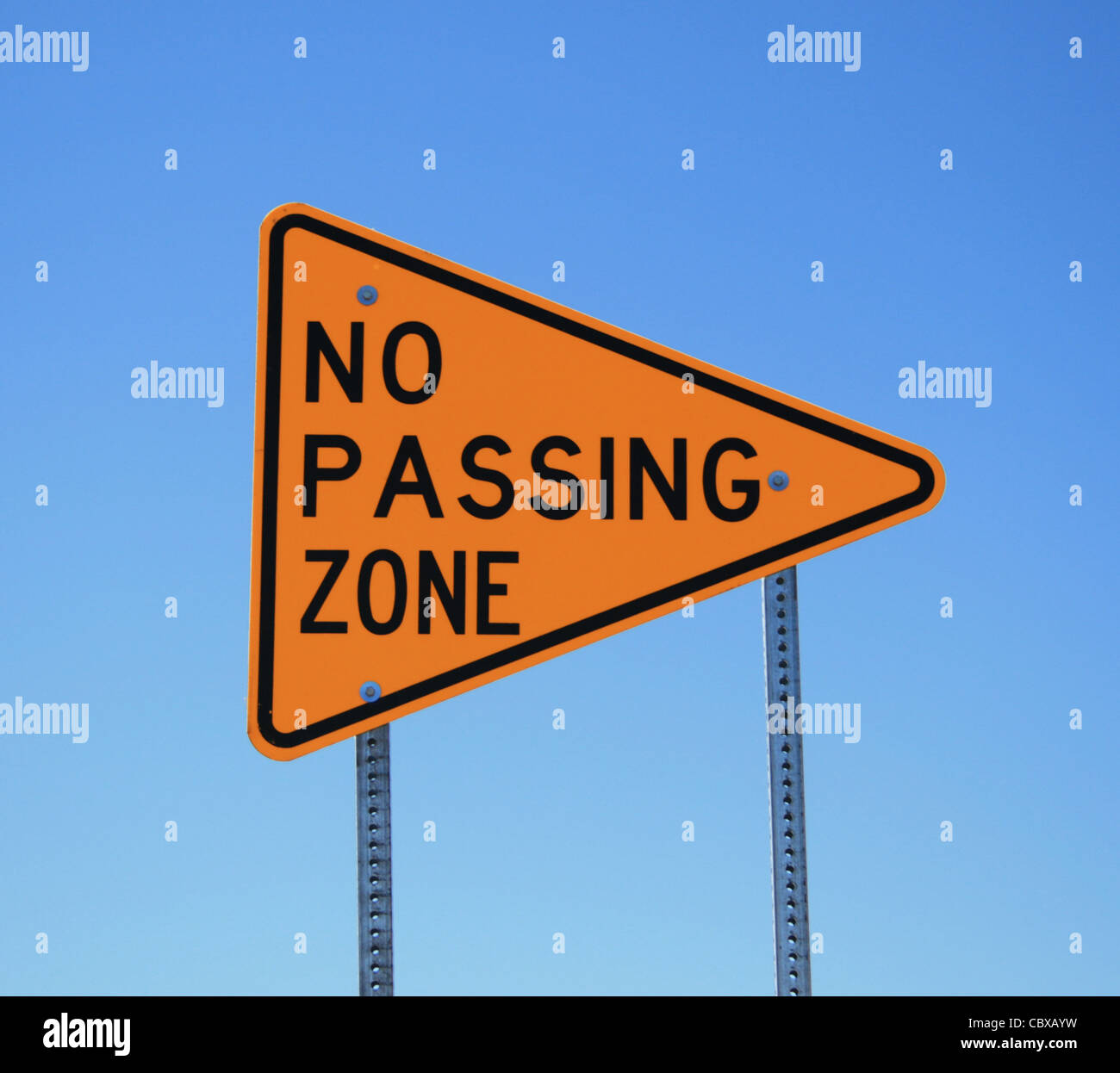 no passing zone road sign in yellow and black on blue sky background - Stock Image