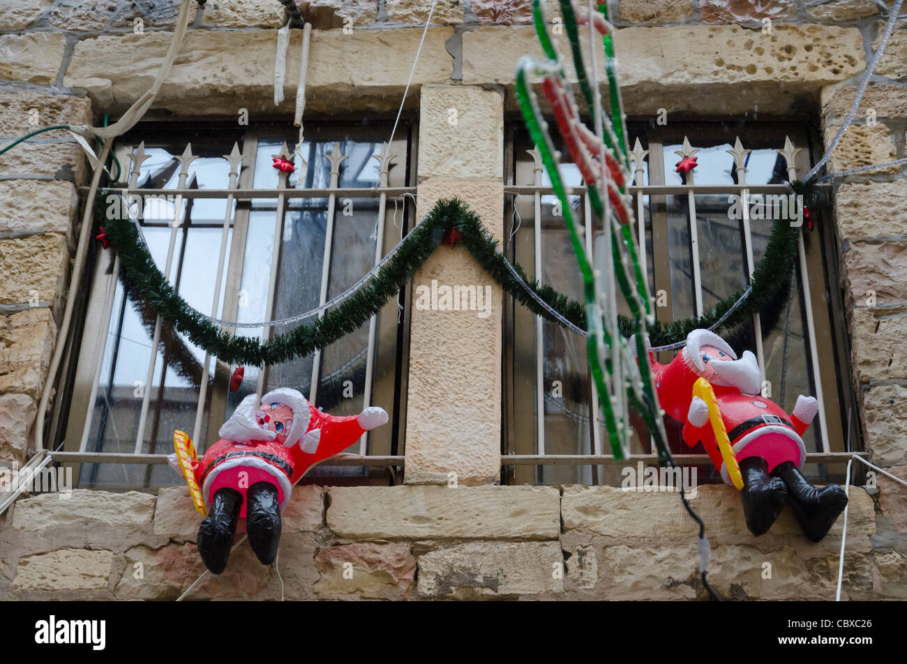 dummies of Santa Klaus hanging at window in Christian Quarter. Jerusalem Old City. israel Stock Photo