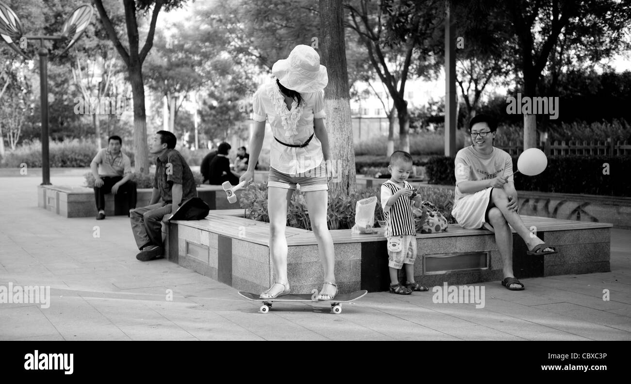 Wukesong, Beijing. Mother, on a skateboard, with child and father in the park. - Stock Image