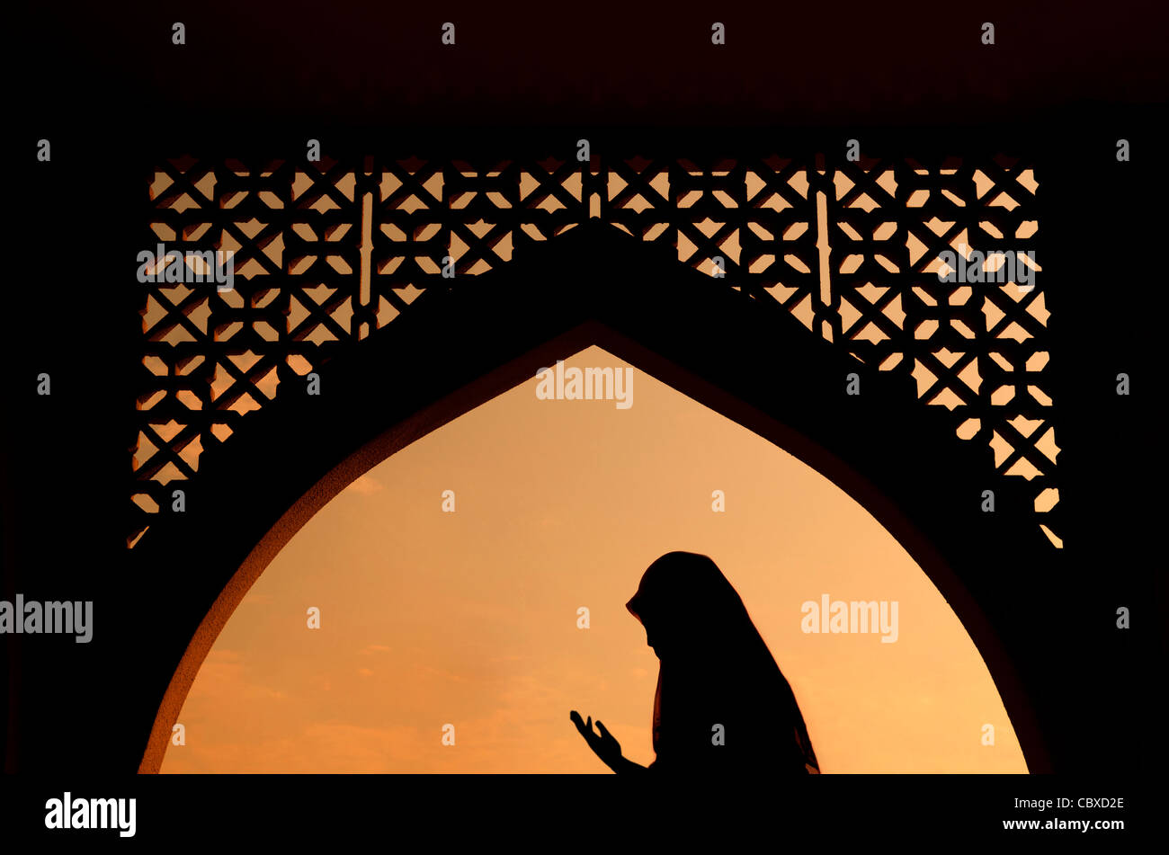 silhoutte of muslim woman praying during fasting holy month of ramadan - Stock Image