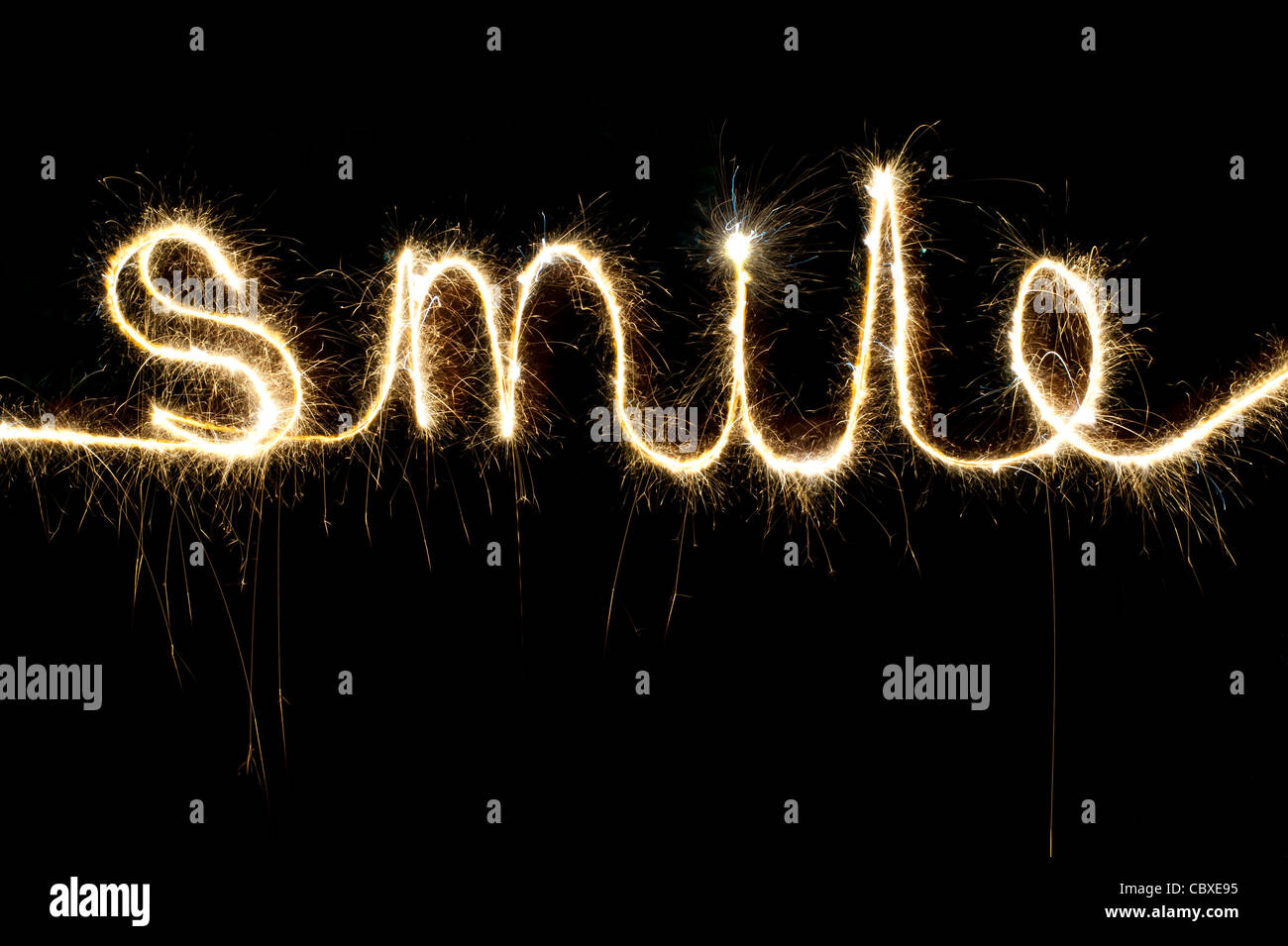 SMILE  written with a sparkler at night - Stock Image