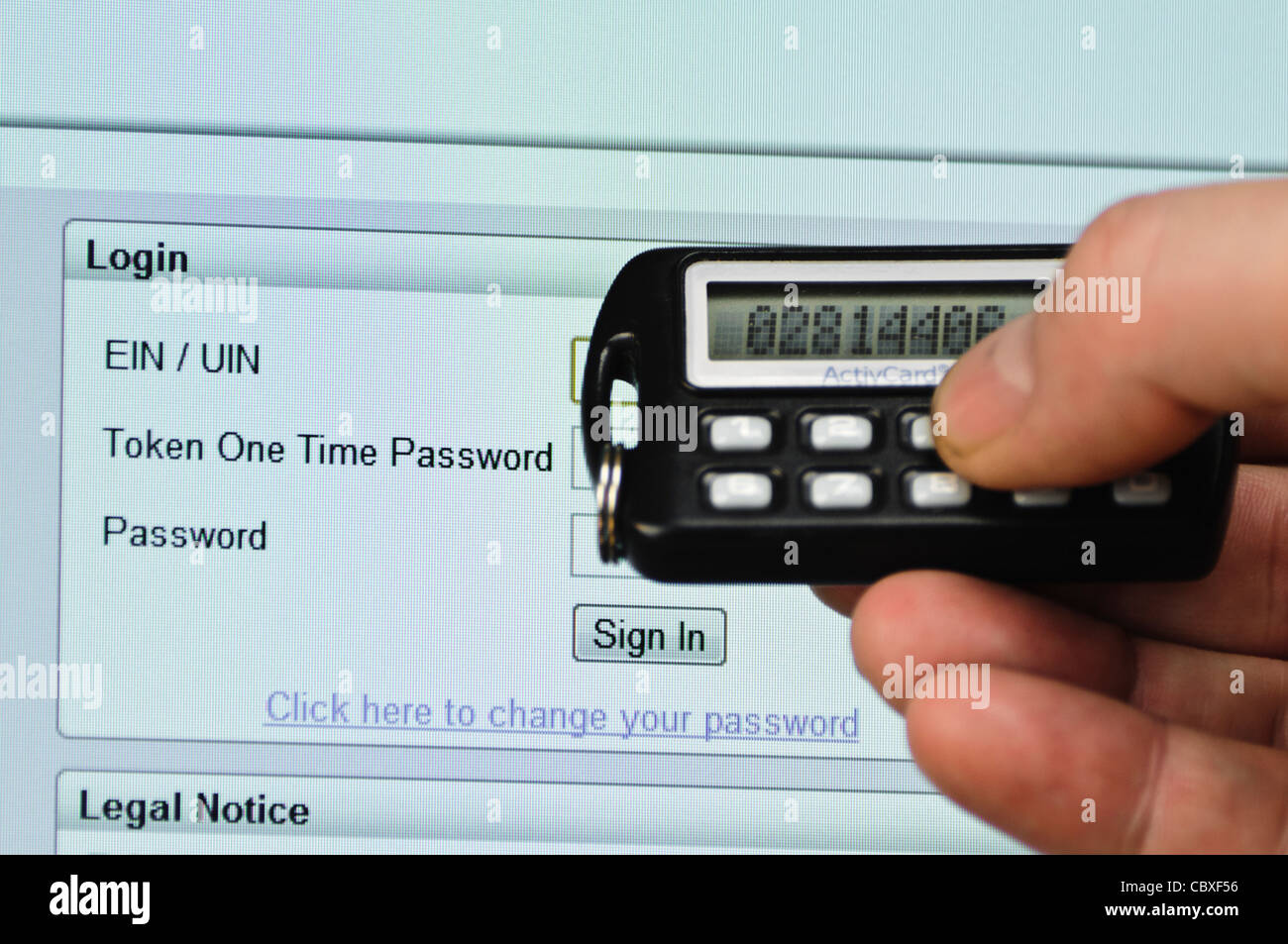Man uses SecureID token to log into a website needing a userID, Passcode and Password - Stock Image