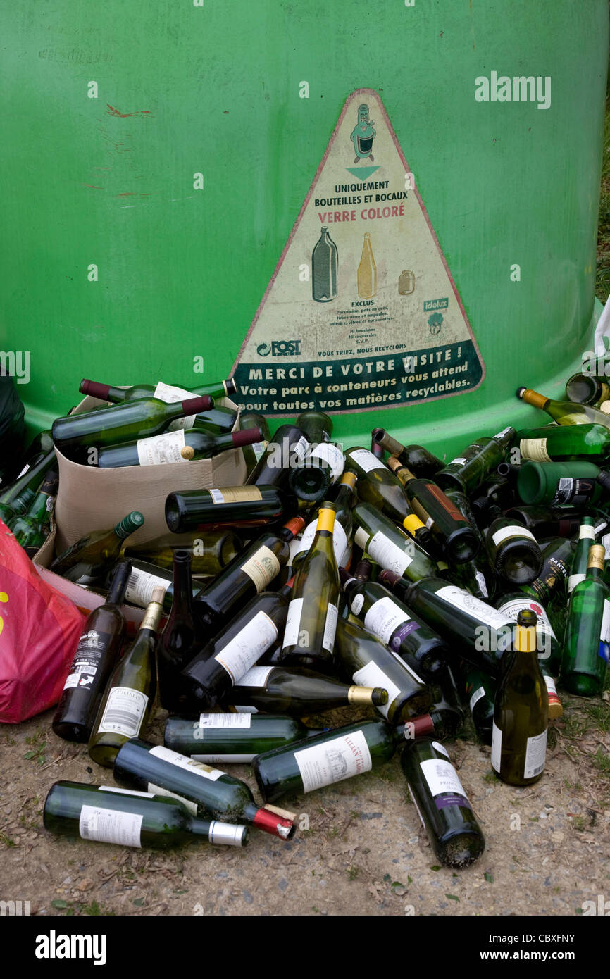 Glass collection point / Bottle bank with dumped wine bottles in front - Stock Image