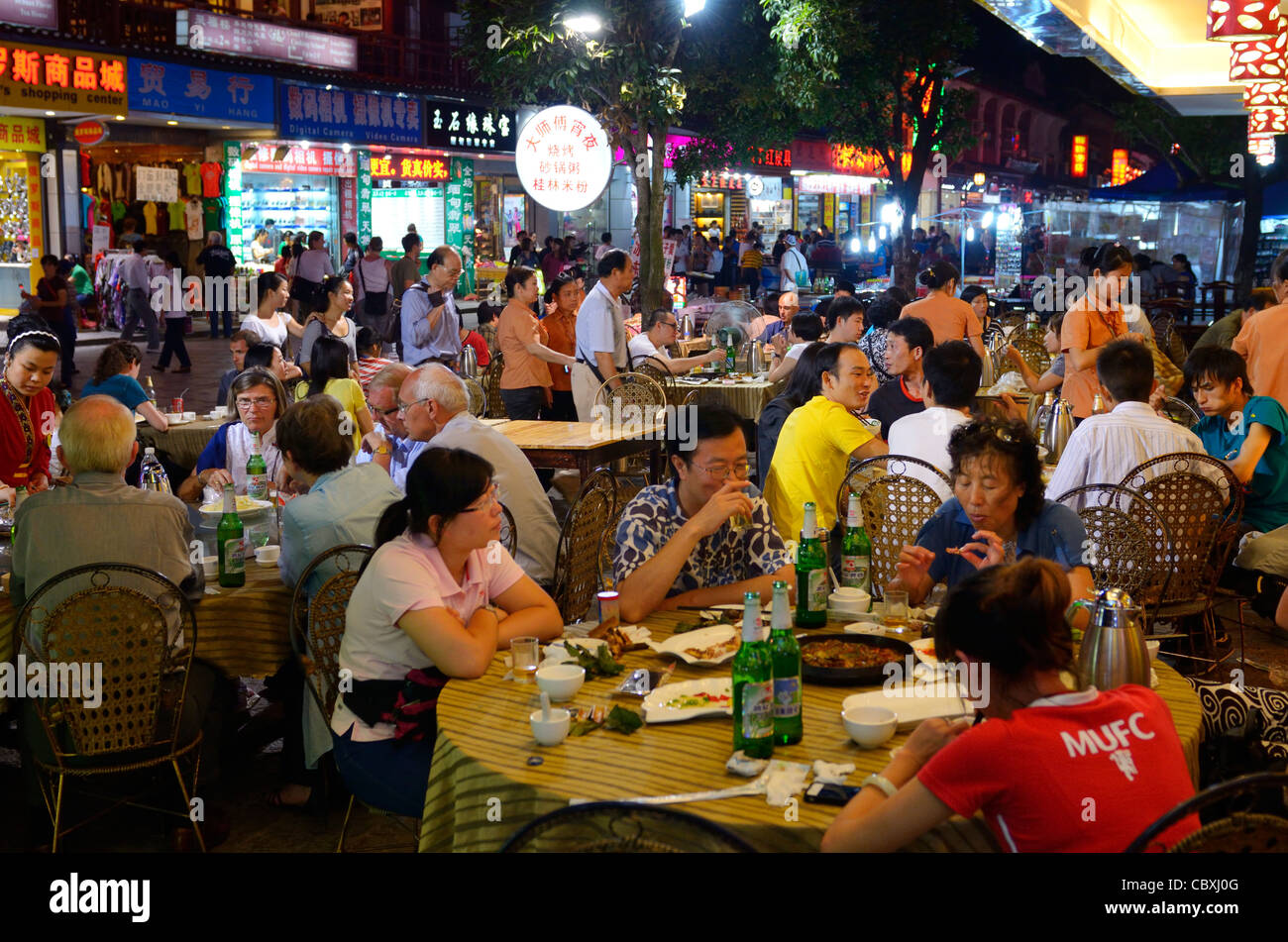 Chinese people eating alfresco at outdoor street restaurant at night in Yangshuo China Stock Photo