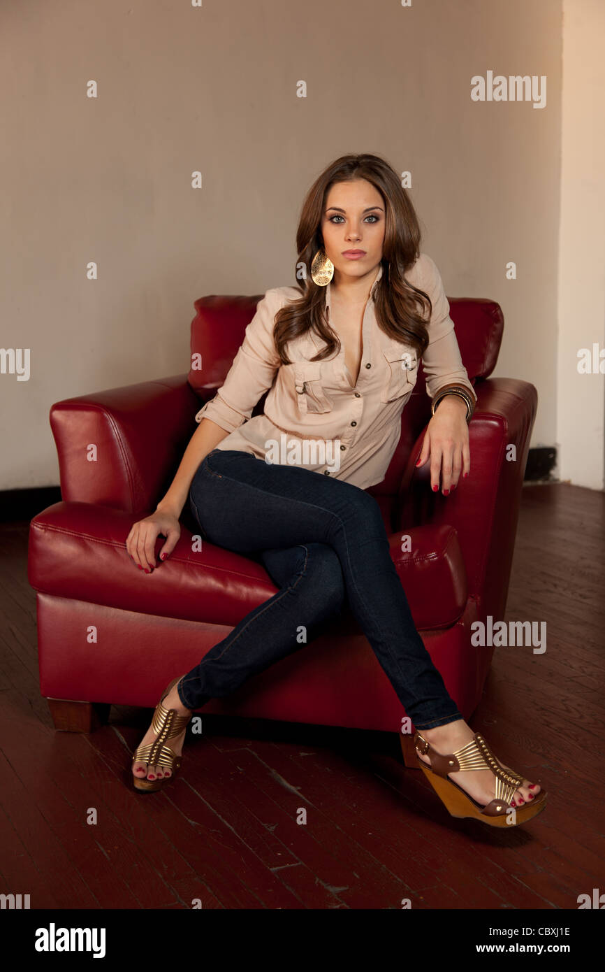pretty caucasian woman sitting in a red leather chair stock photo  41766858