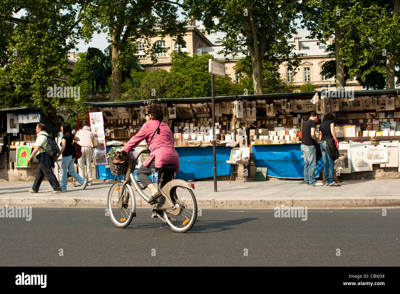 Cyclist in Paris traveling past a Bookseller on the Quai  de Montebello along the banks of the Seine - Stock Image