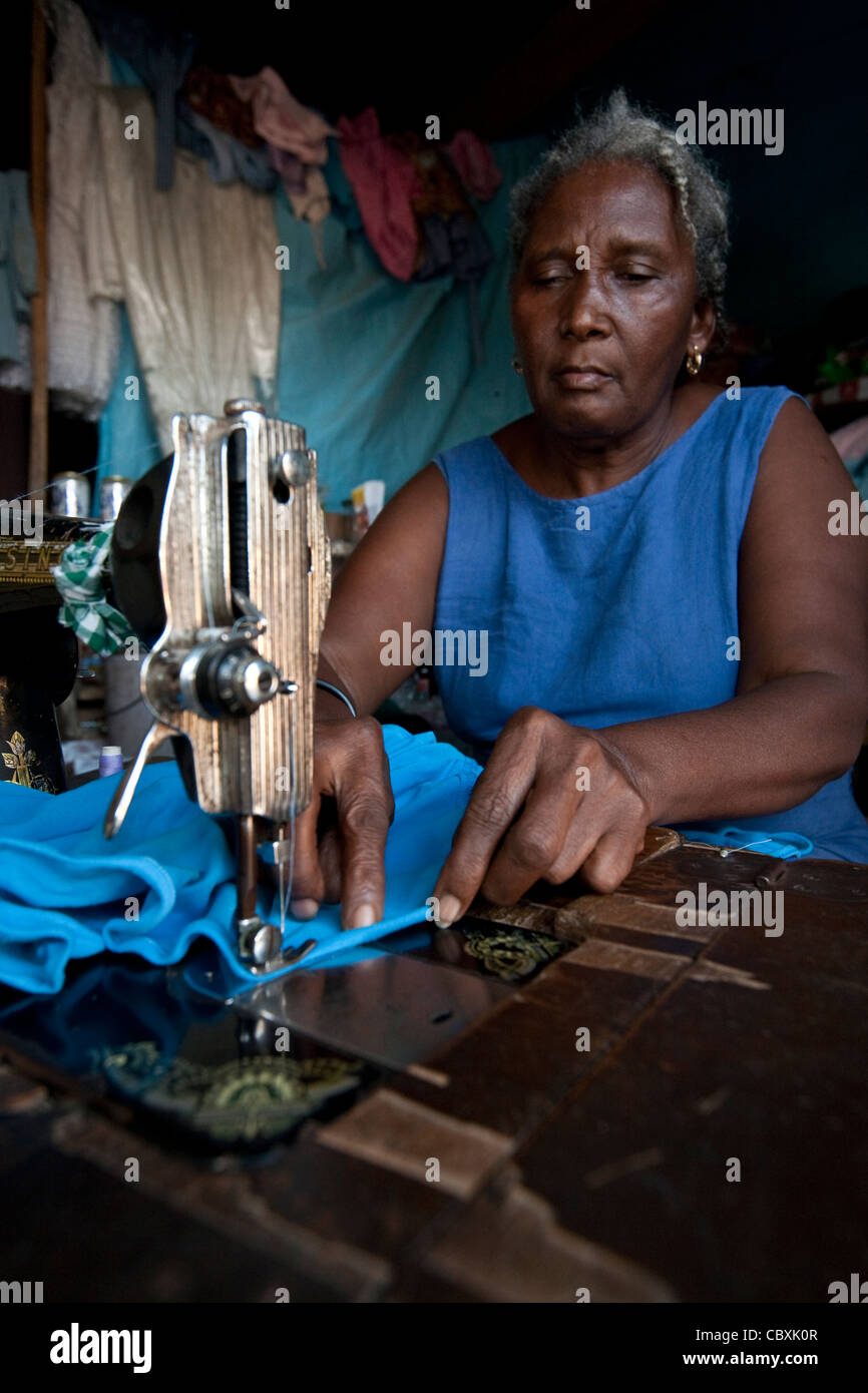 A taylor works in her alterations shop in Mirebalais, Haiti. - Stock Image