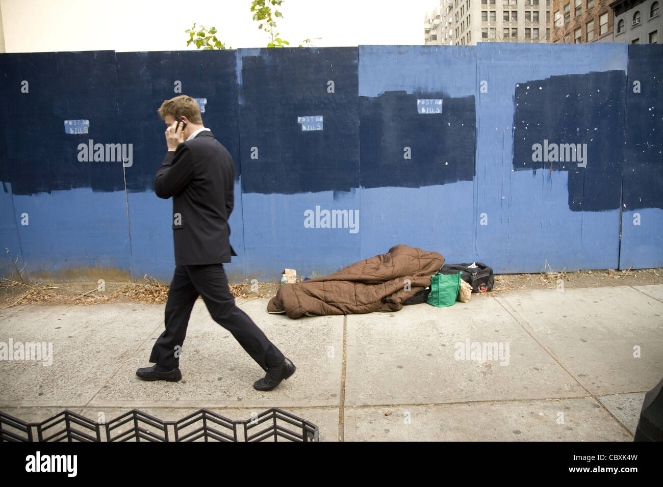 Homeless person asleep on the sidewalk in midtown Manhattan. - Stock Image