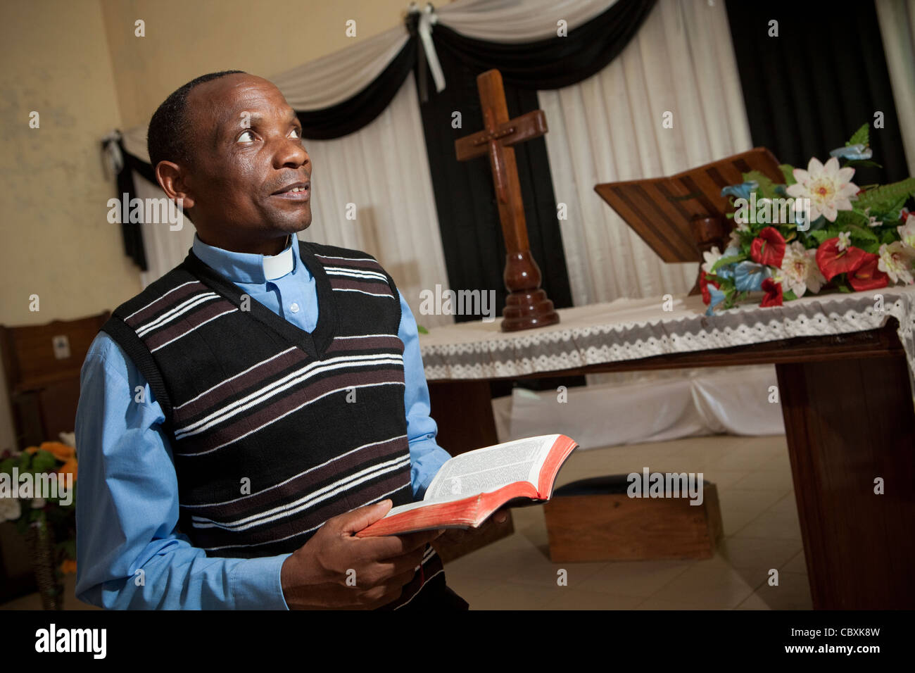 A priest stands at the altar of a church in Morogoro, Tanzania, East Africa. - Stock Image