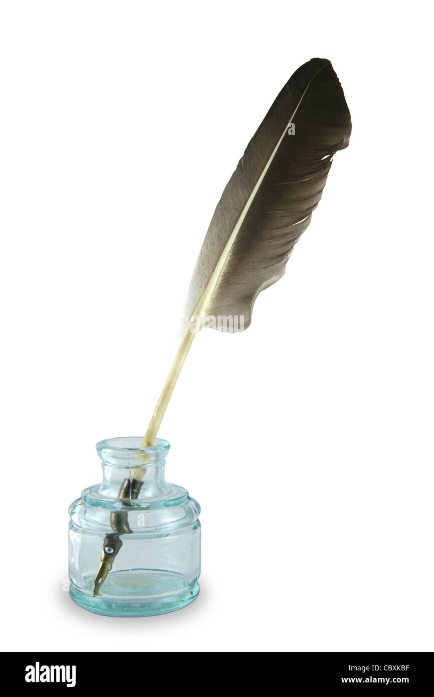 Feather quill pen in a circa 1890s to 1940s glass inkwell. - Stock Image