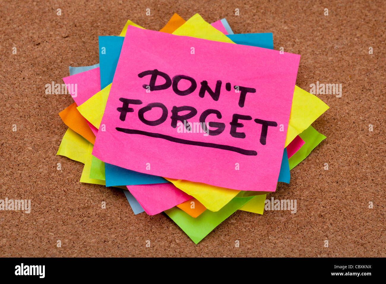 do not forget reminder - a stack of colorful sticky notes on cork bulletin board - Stock Image