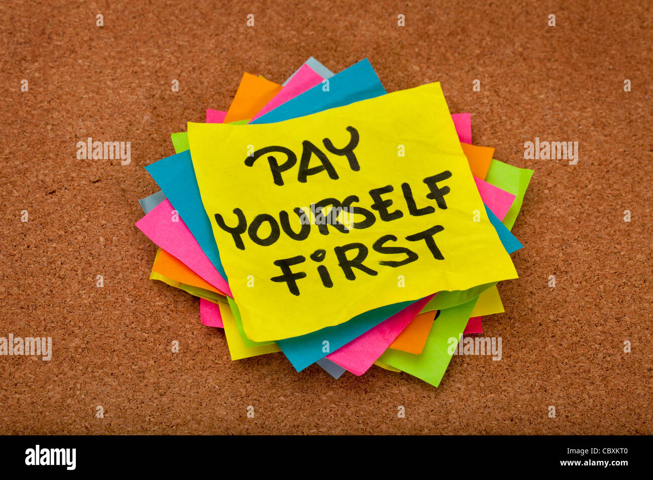 pay yourself first, a reminder of personal finance strategy - stack of colorful sticky notes on a cork bulletin - Stock Image