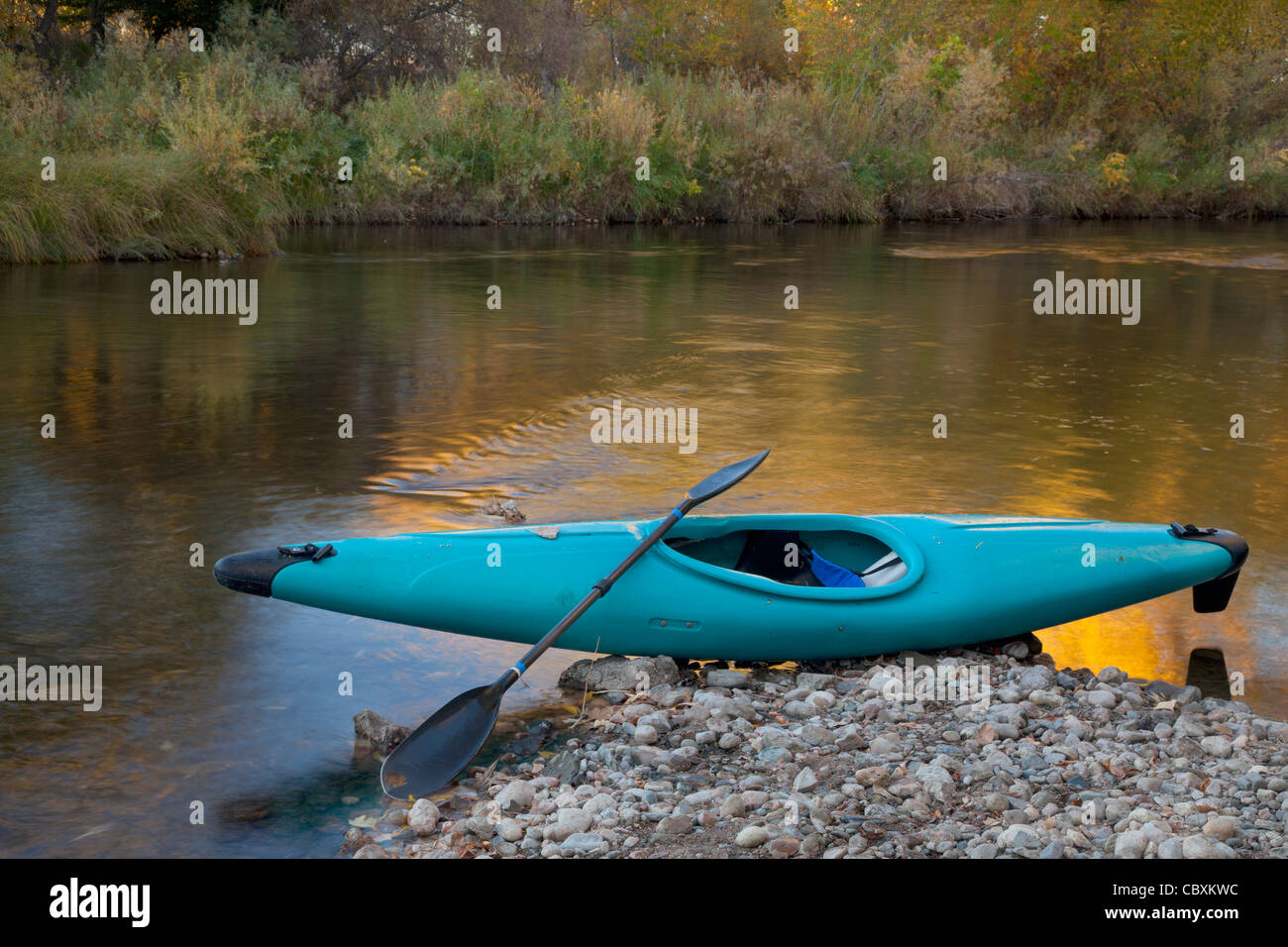 blue whitewater kayak on a rocky shore against river with gold color reflection - Stock Image