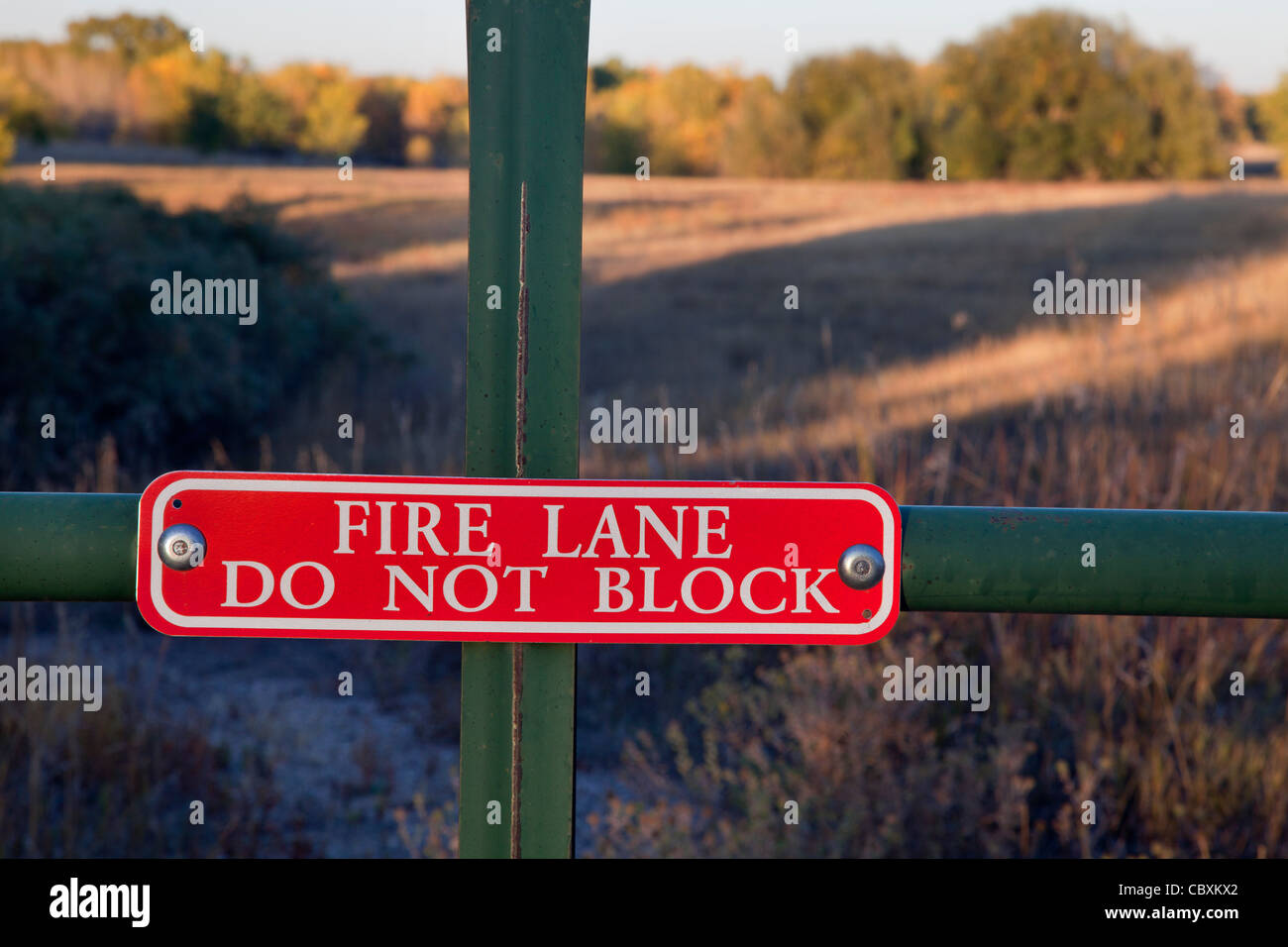 fire lane, do not block sign on a gate with a meadow and woods landscape behind - Stock Image