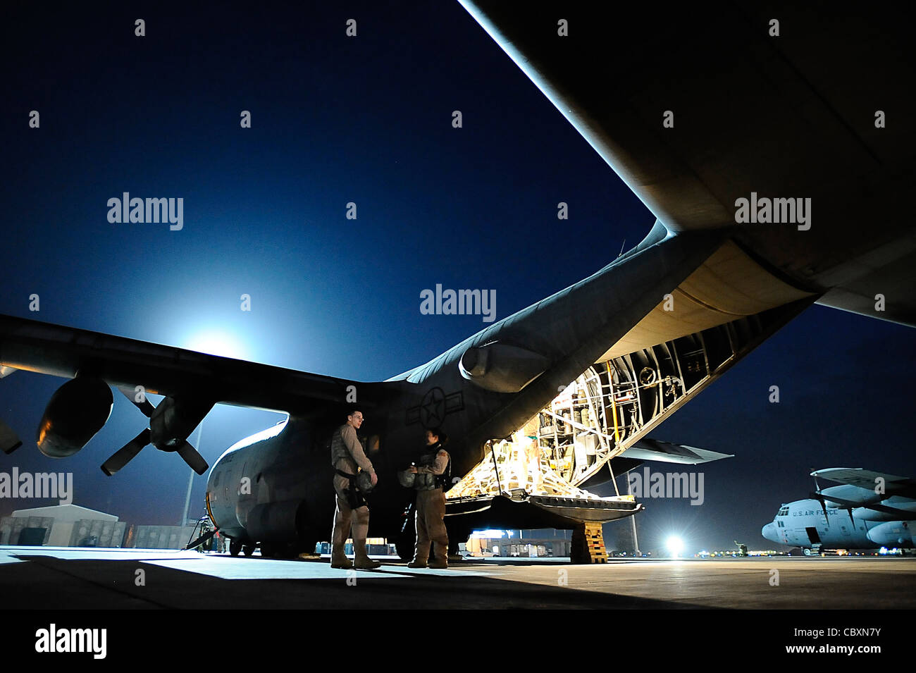 Senior Airmen Matthew Rinehart and Rosie Munoz stand outside of a C-130 Hercules Dec. 31, 2008, at Joint Base Balad, - Stock Image