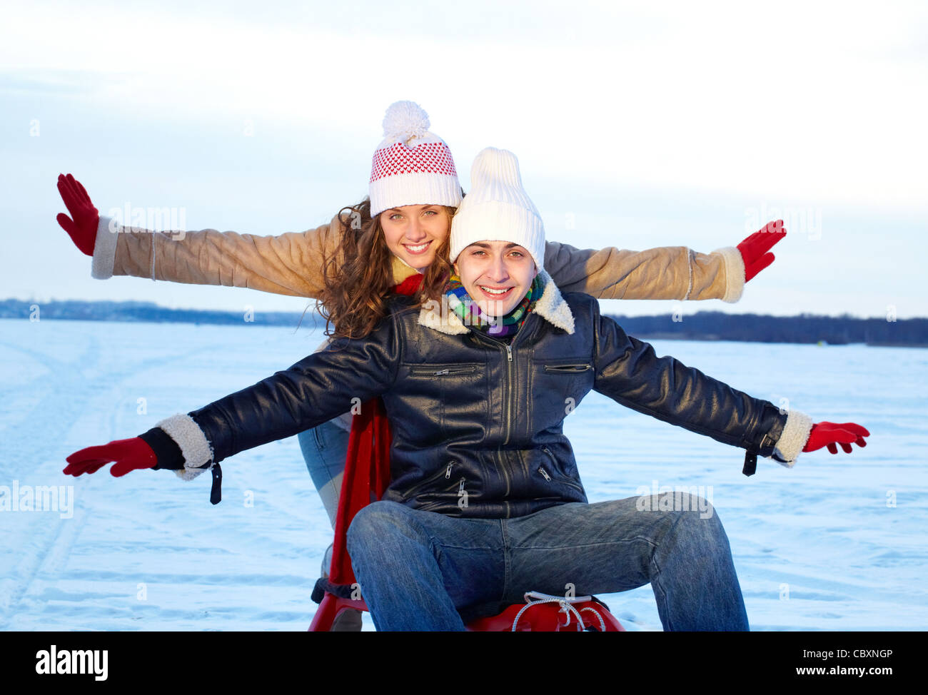 Portrait of happy couple in warm clothes having nice time in winter - Stock Image