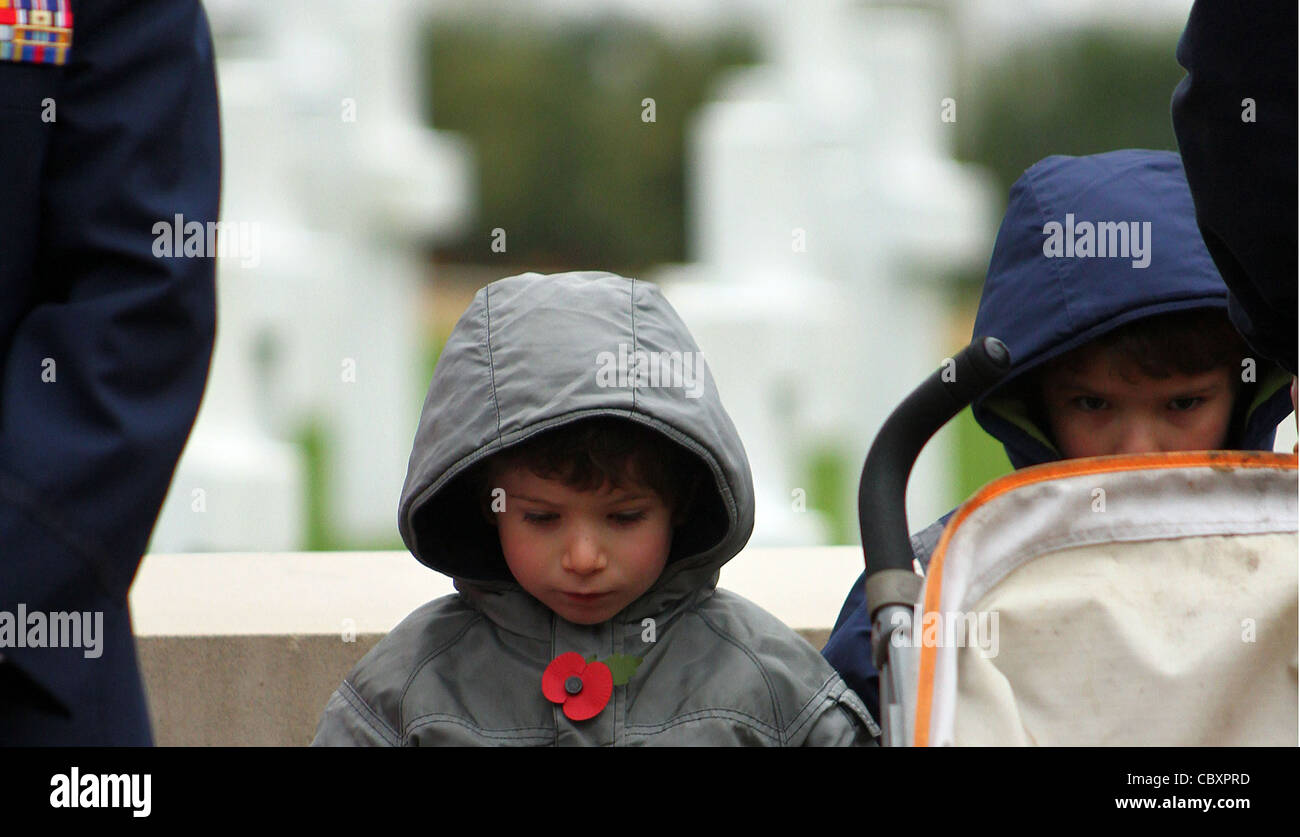 A young boy wearing a poppy bows his head in respect at a remembrance day parade. - Stock Image