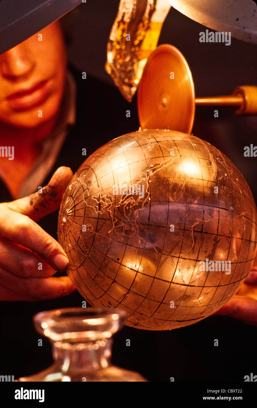 Craftsman cuts lines on a crystal world globe in Waterford Crystal factory, Waterford, Ireland - Stock Image