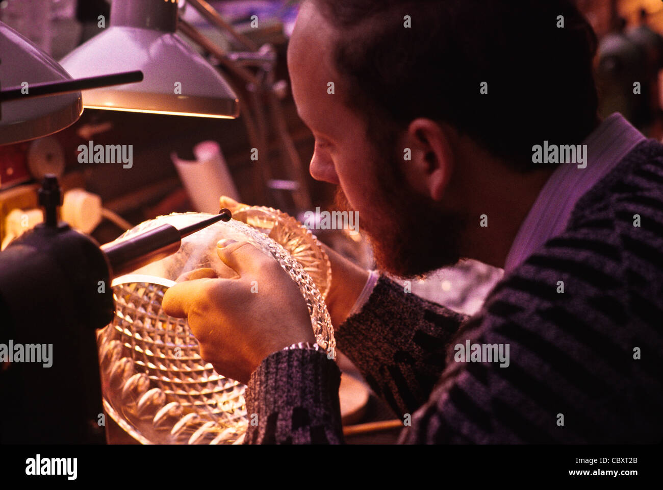 Engraver adds final touches to crystal trophy bowl in Waterford Crystal factory, Waterford, Ireland - Stock Image