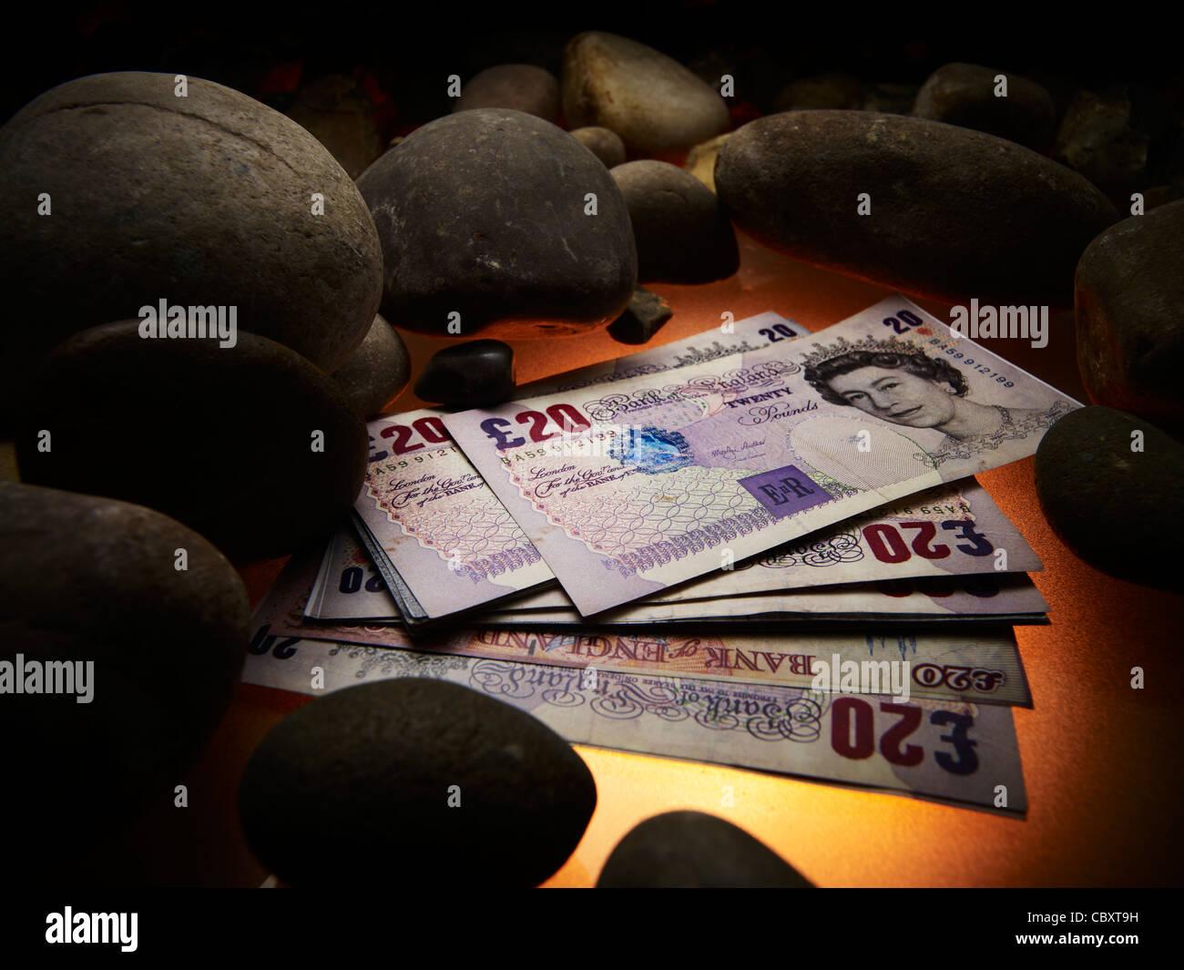 Twenty pound notes next to stones - Stock Image
