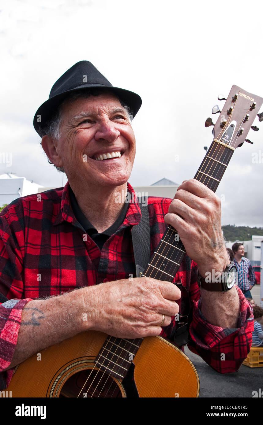 Busker with guitar in Dunedin Farmers Market - Stock Image