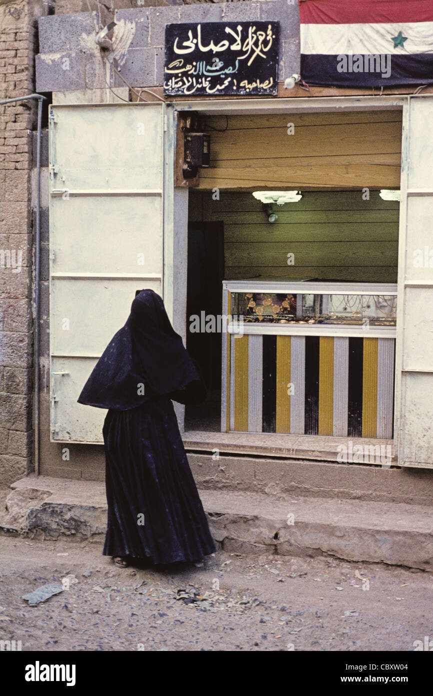 A Yemini woman wearing traditional abaya in front of a jewelry store in the Old City of Sana'a, Yemen - Stock Image