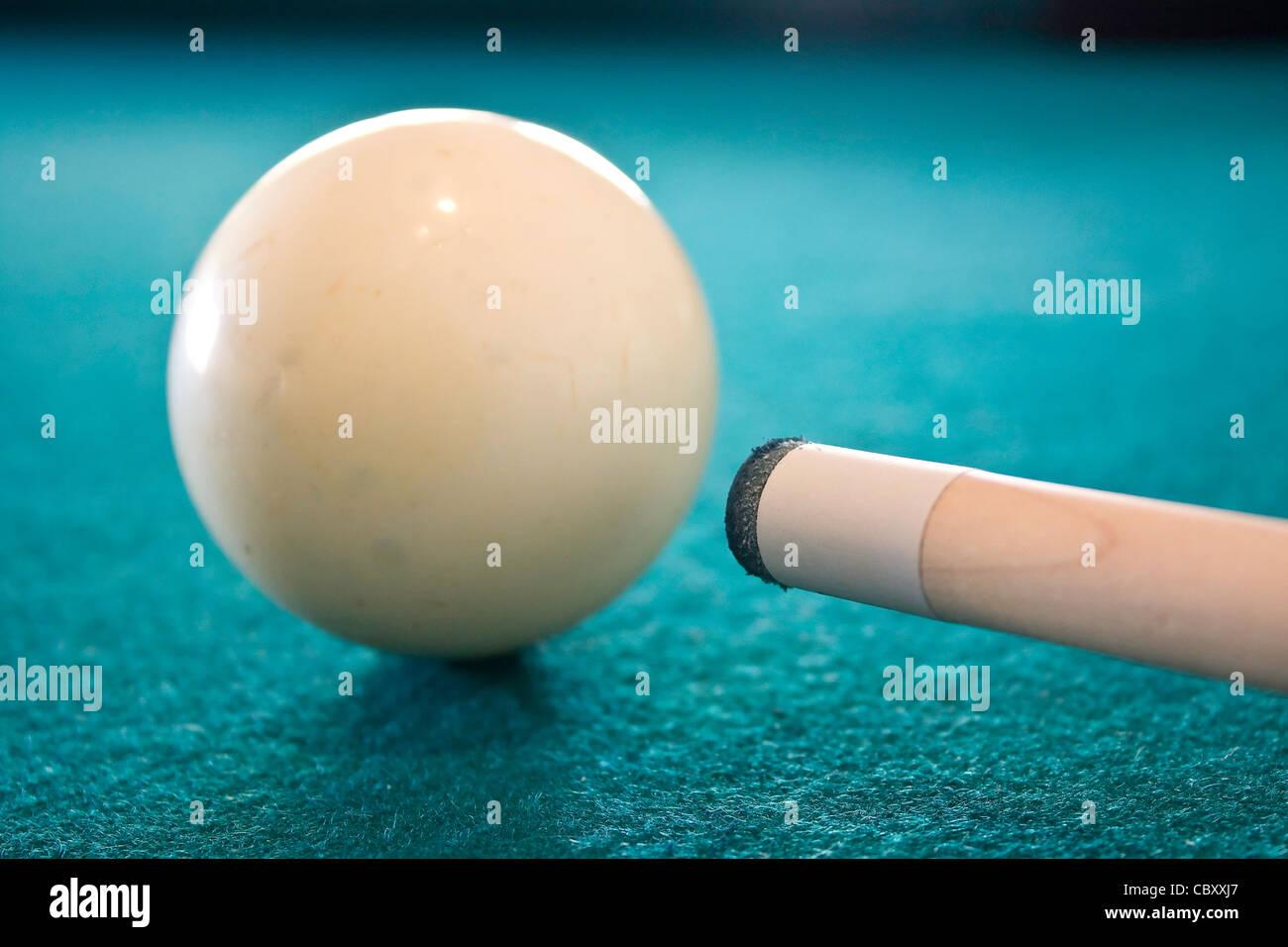 Billiard ball and cue stick macro - Stock Image