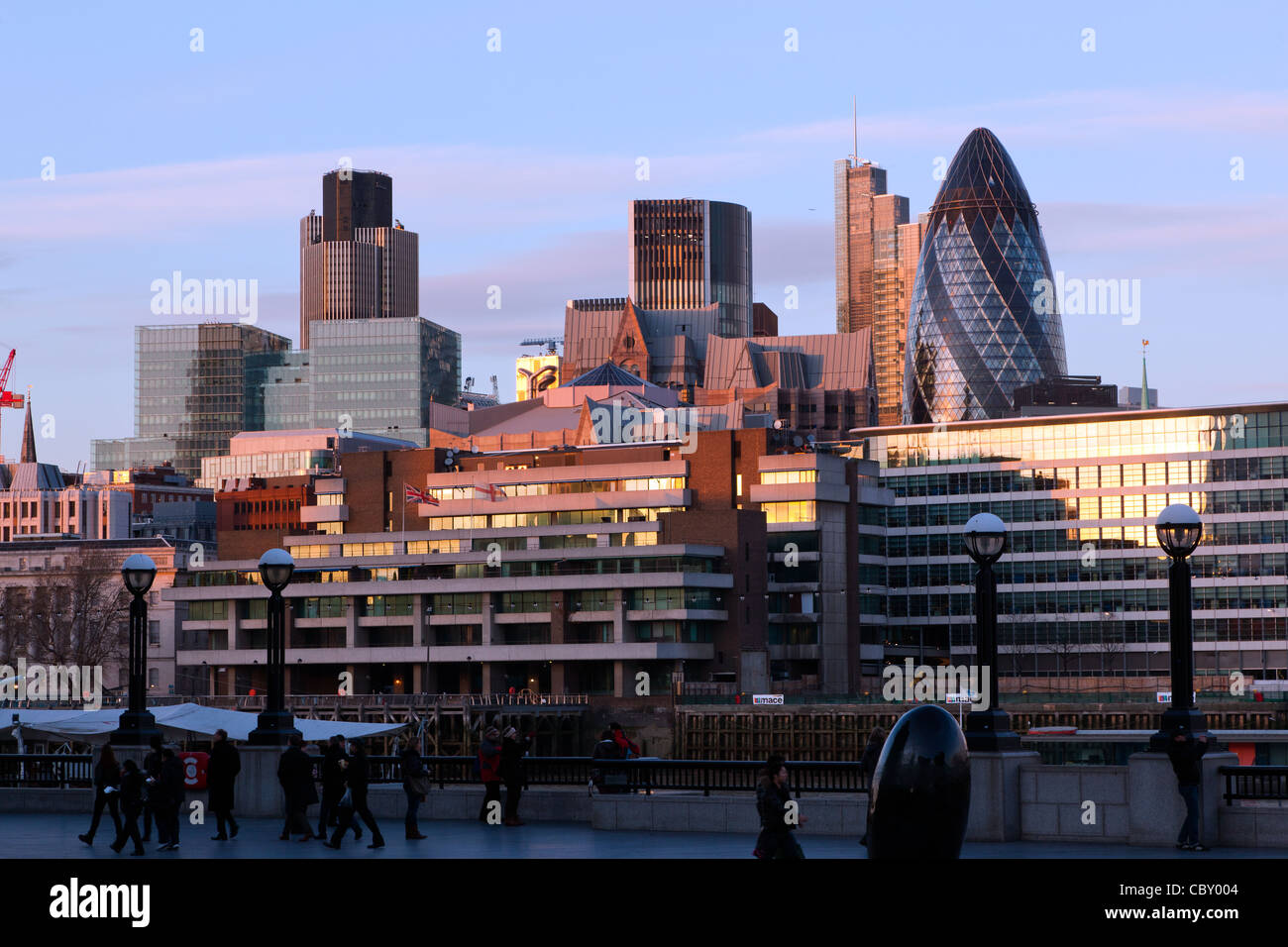 Looking towards the Financial District from South Bank, London at sunset. The famous 'Gherkin' (Swiss Re - Stock Image