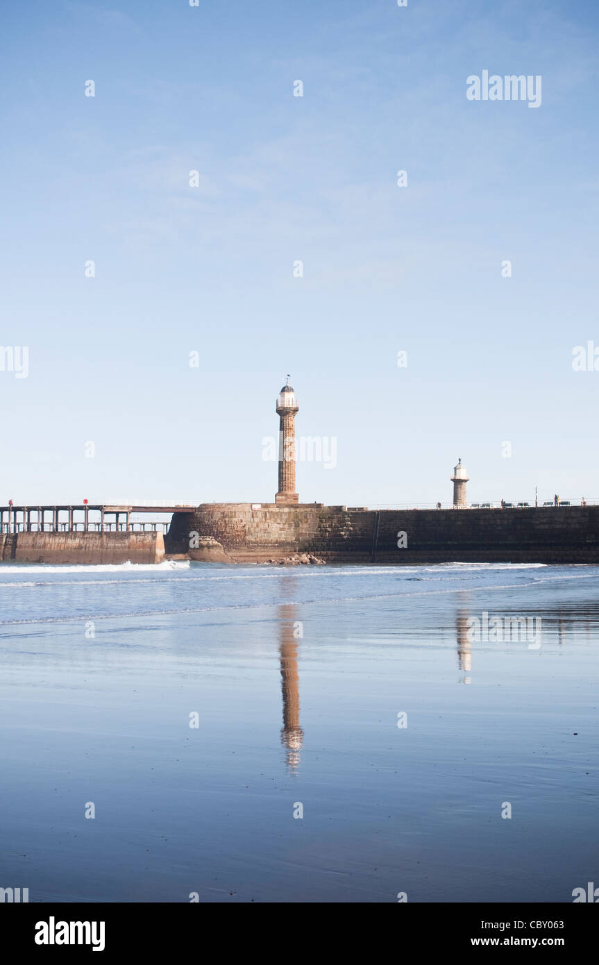 A view of a lighthouse on Whitby Pier with reflection in Whitby Beach, on a bright Spring day. Whitby, North Yorkshire, - Stock Image
