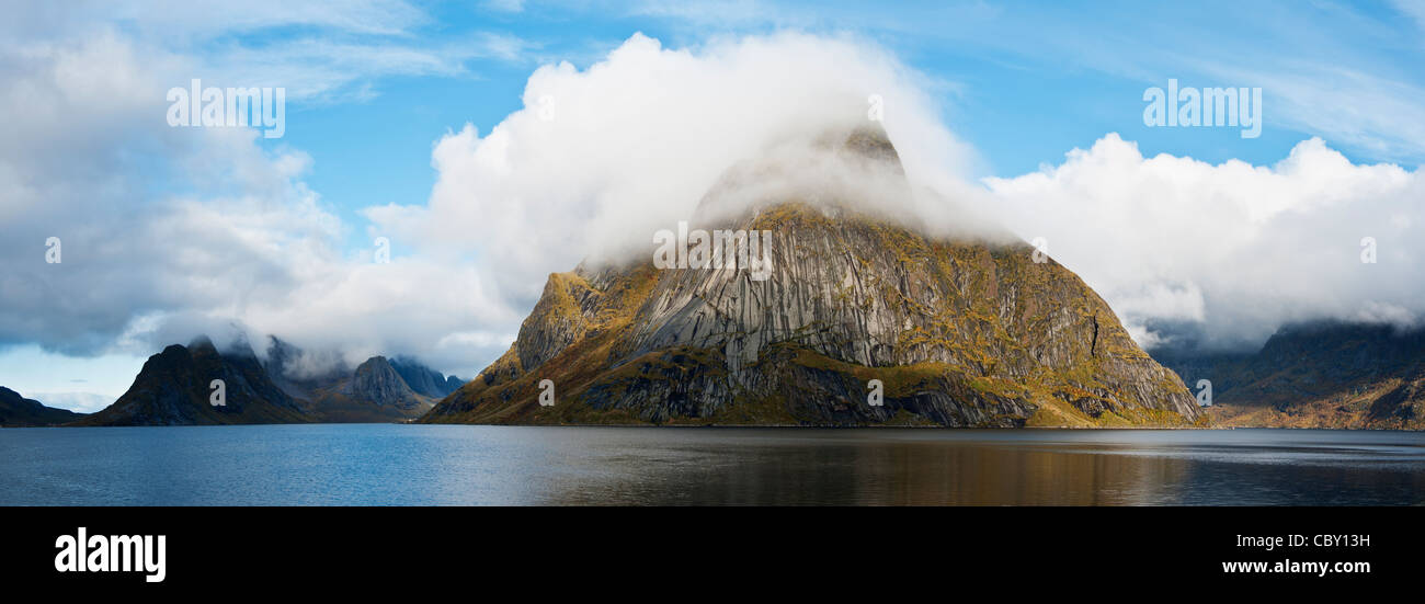 Cloud covered Olstinden mountain peak rises from Kjerkfjord, Reine, lofoten Islands, Norway Stock Photo