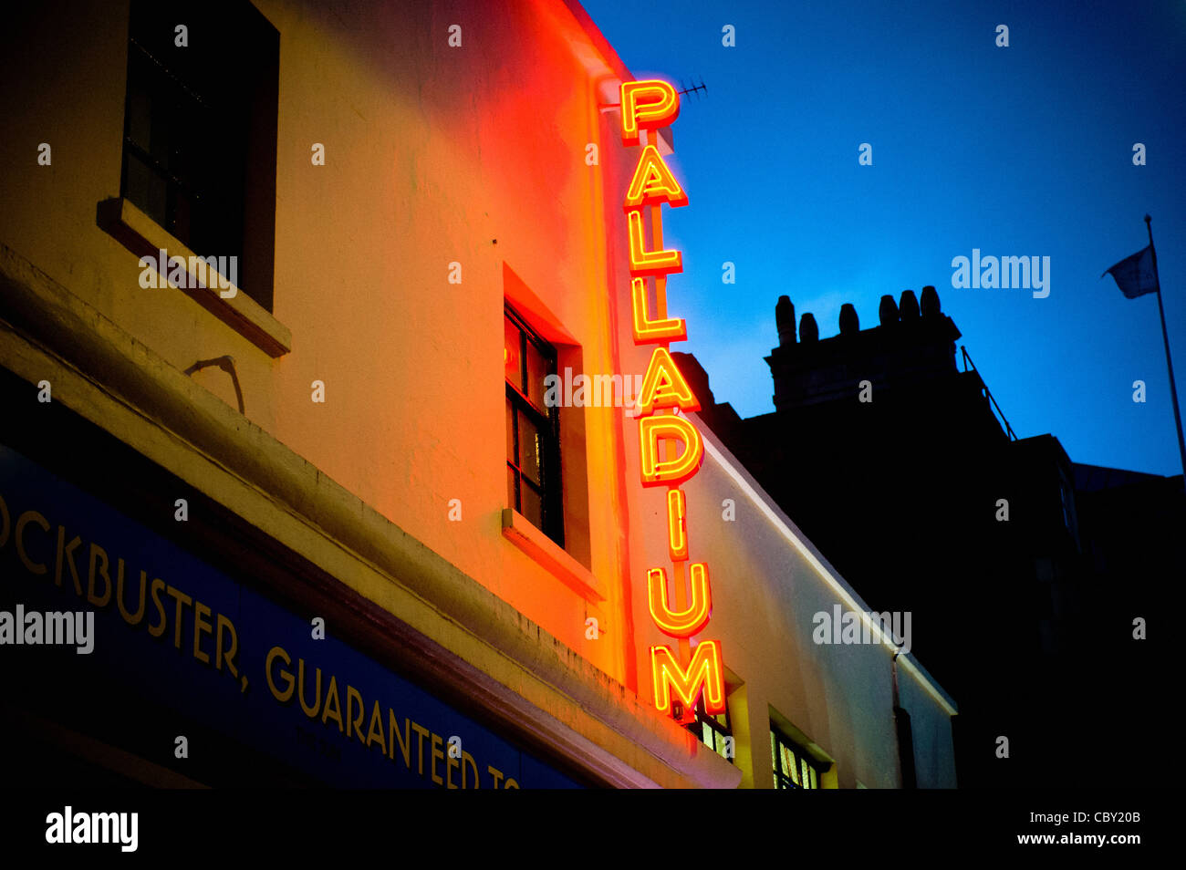 Red and yellow neon sign outside Palladium theatre, London. - Stock Image