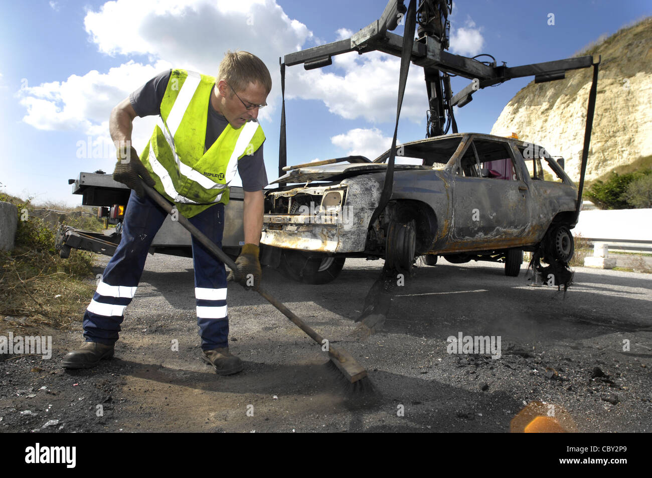 Burned out car being removed - Stock Image