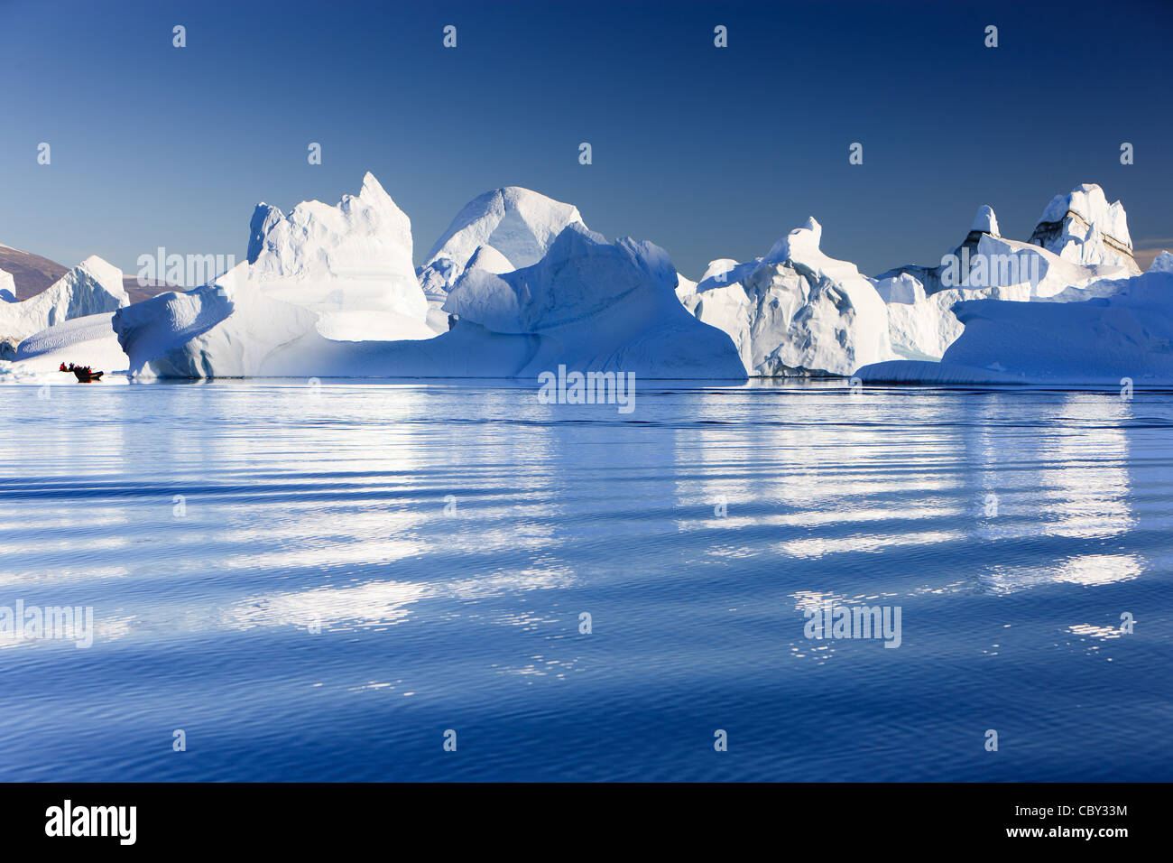 Cruising between the icebergs at Røde Ø, Scoresby sund, Greenland Stock Photo