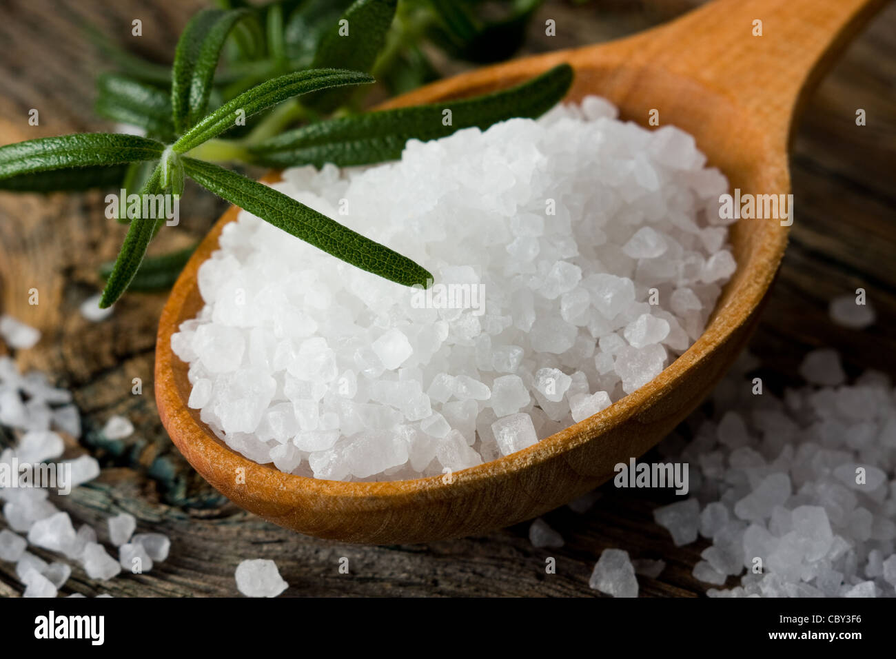 Rosemary and healthy sea salt on wooden spoon closeup - Stock Image