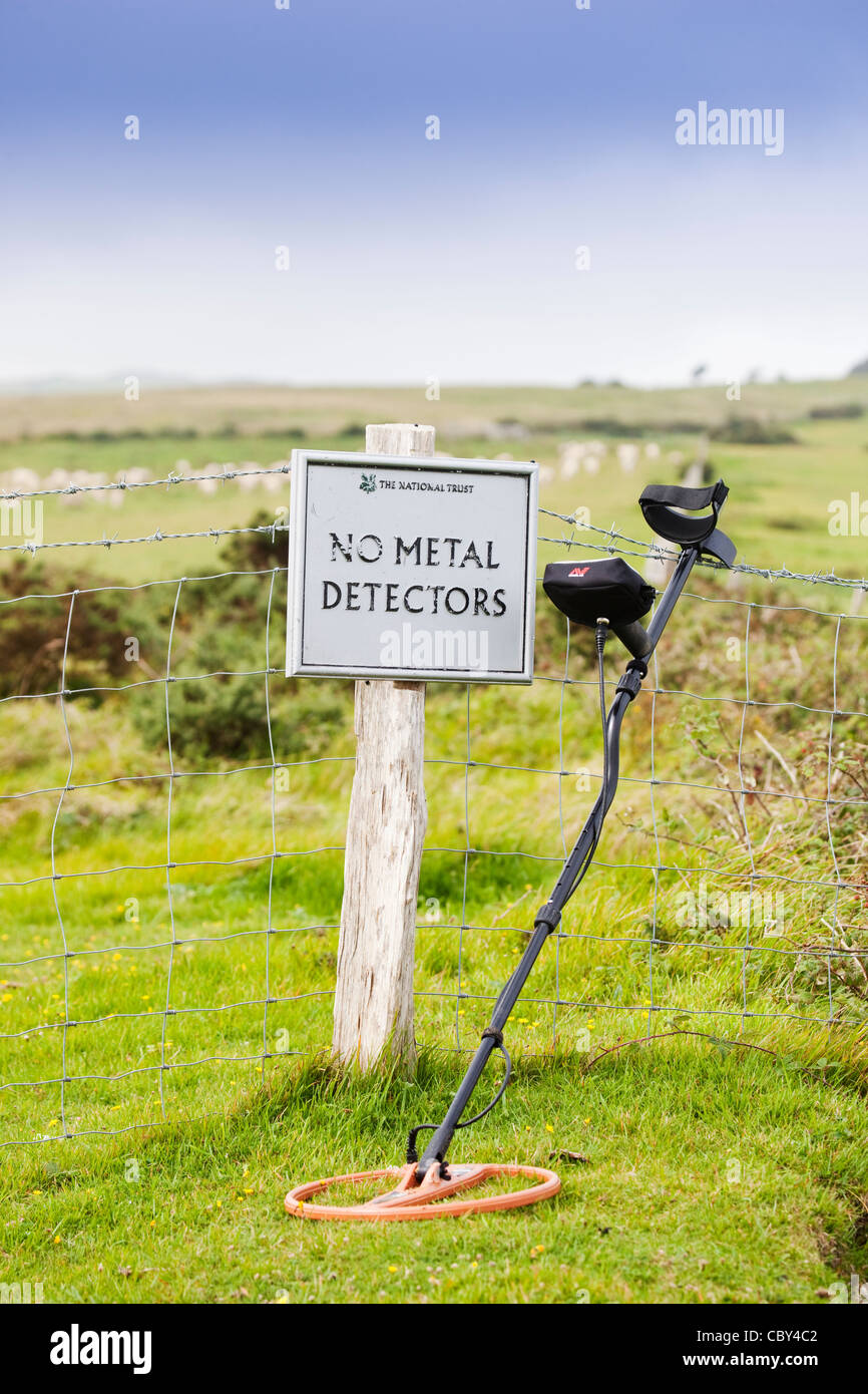 Metal detector lean on to a fence. - Stock Image