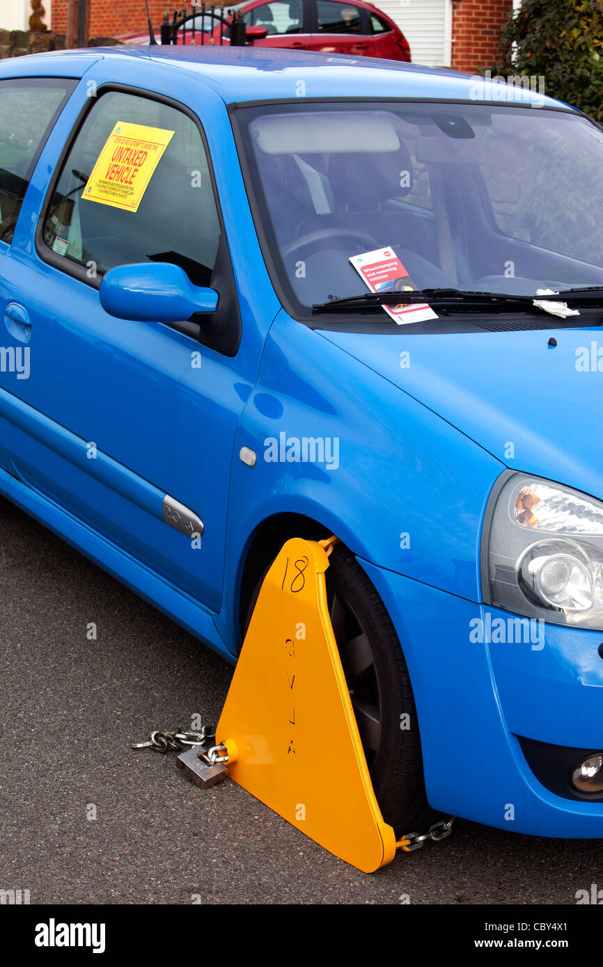 Untaxed vehicle with DVLA wheel clamp on a UK street Stock Photo